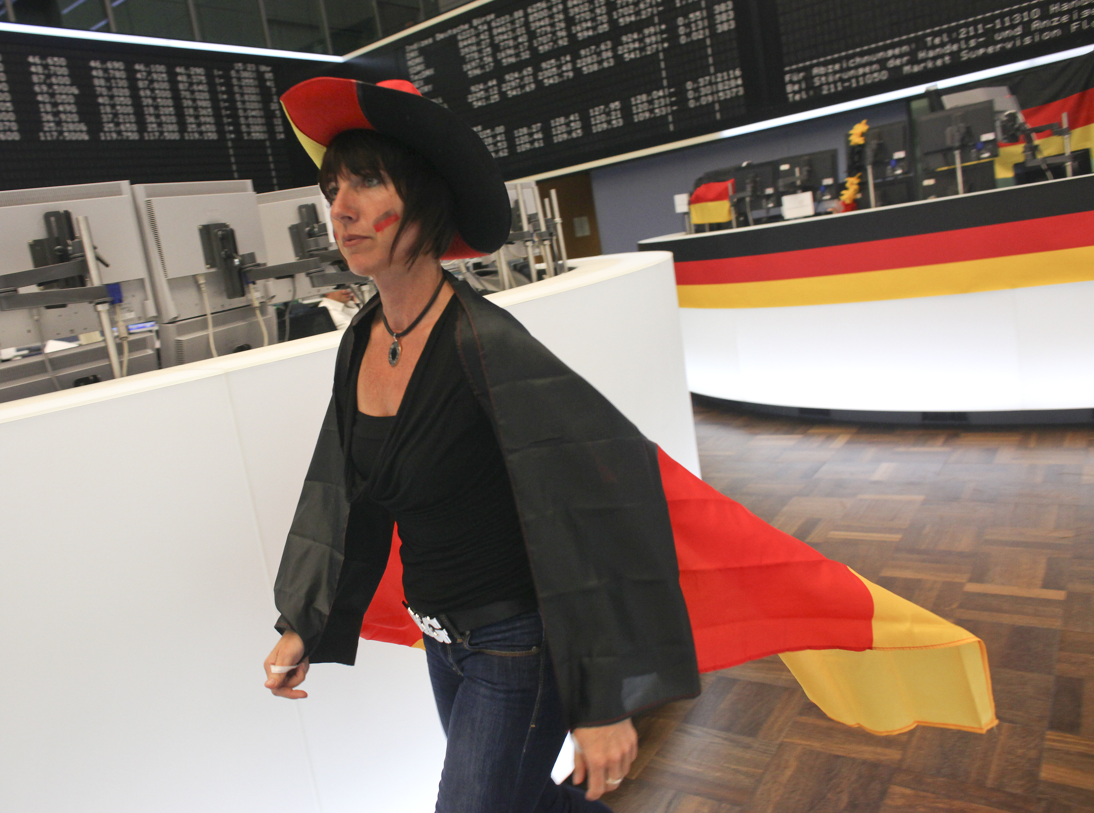 A trader wrapped in a German flag walks across the trading floor of Frankfurt stock exchange during a live broadcast of the 2010 World Cup soccer match between Germany and Serbia in Frankfurt June 18, 2010.  REUTERS/Ralph Orlowski (GERMANY - Tags: SPORT SOCCER WORLD CUP BUSINESS) - RTR2FD2R