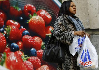 A woman carries a Tesco shopping bag outside a branch of the supermarket in London.