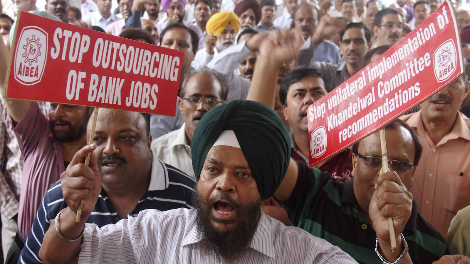 A bank employee shouts slogans while holding placards at a rally during a two-day strike in the northern Indian city of Chandigarh August 22, 2012