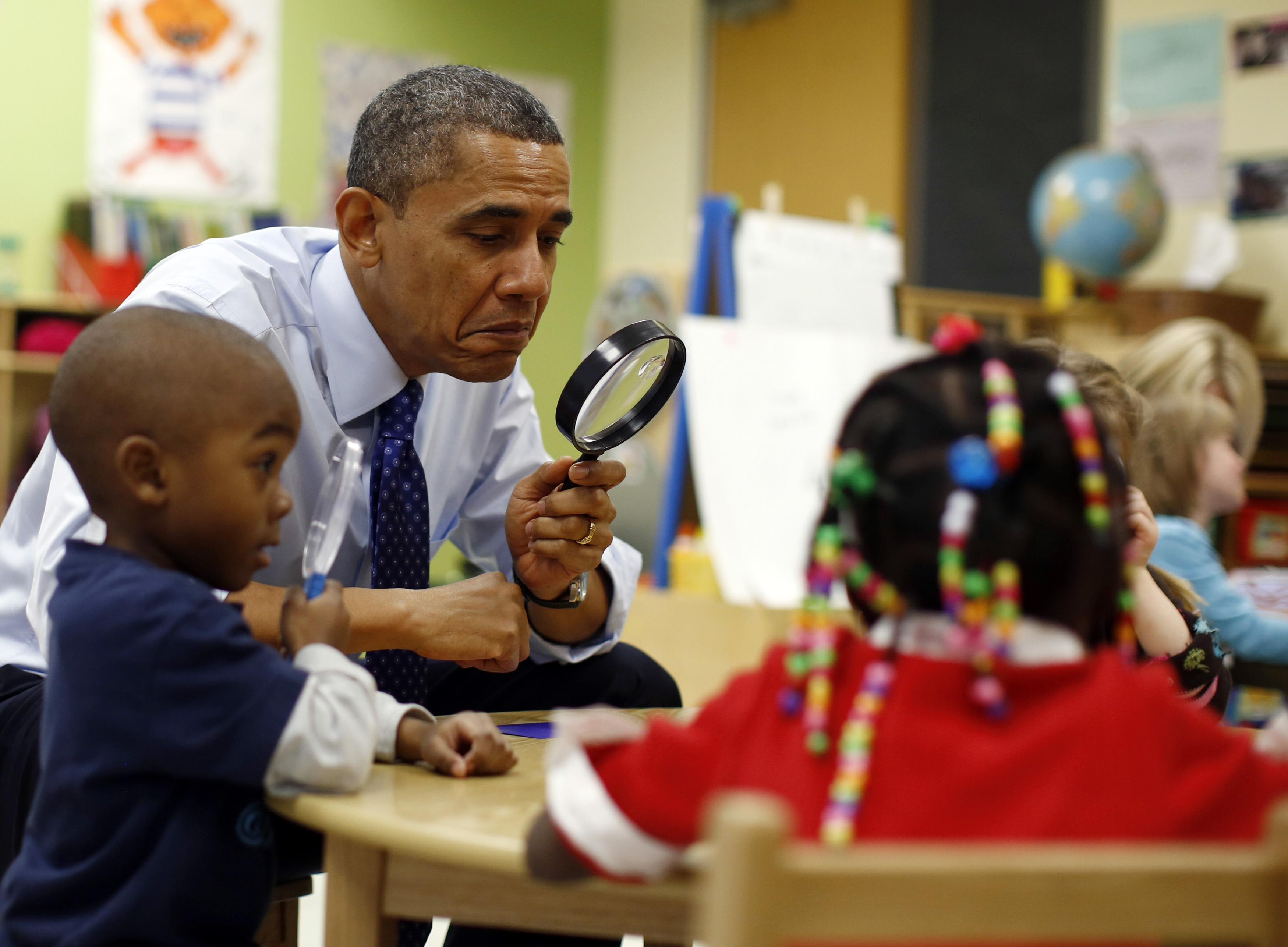 U.S. President Barack Obama uses a magnifying glass to play a game with children in a pre-kindergarten classroom at College Heights early childhood learning center in Decatur February 14, 2013. Obama flew to Georgia to push his plan to ensure high-quality preschool, unveiled during his State of the Union address this week.  REUTERS/Jason Reed   (UNITED STATES - Tags: POLITICS EDUCATION TPX IMAGES OF THE DAY) - RTR3DSJL