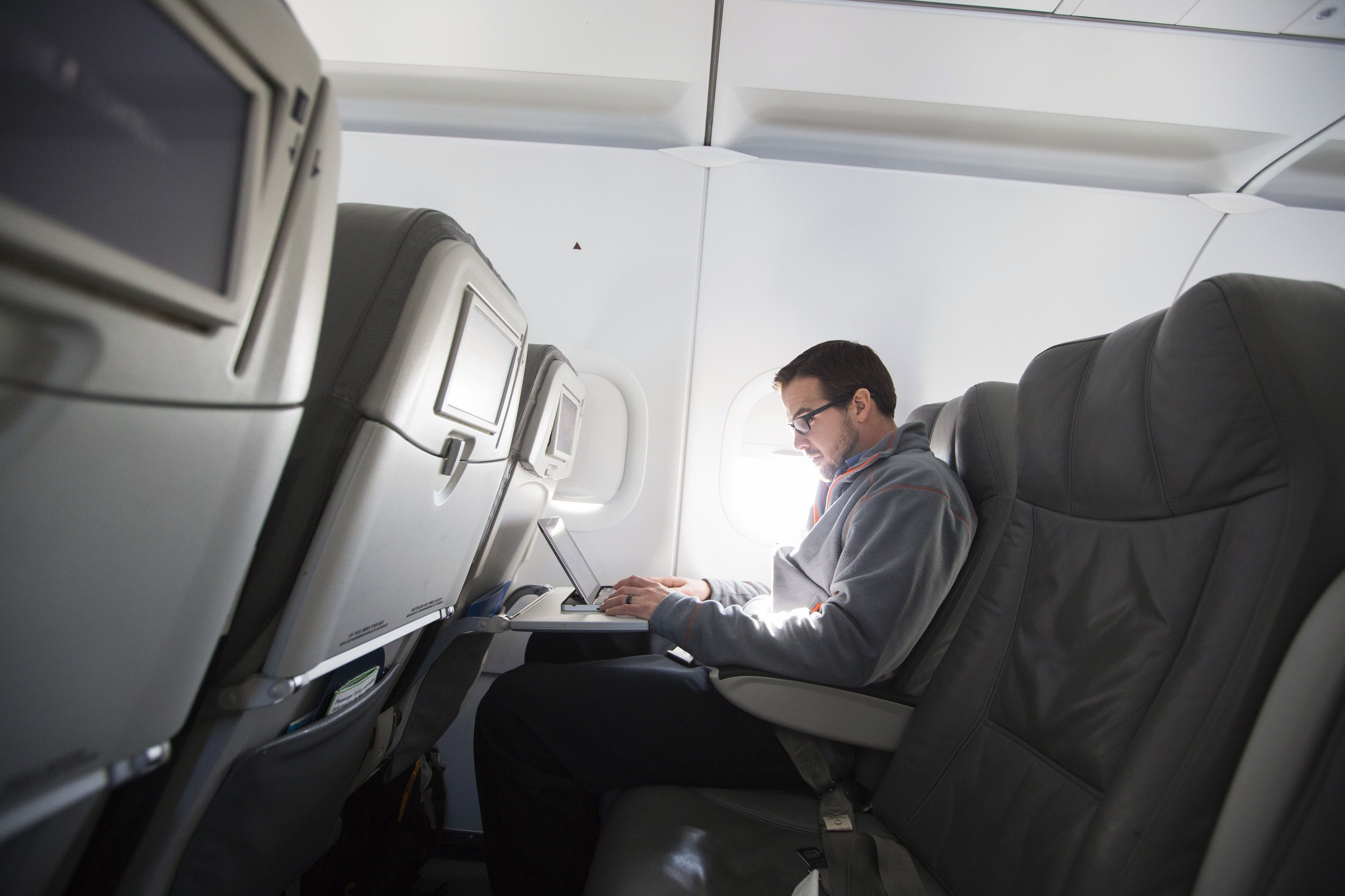 A man uses his laptop to test a new high speed inflight Internet service named Fli-Fi while on a special JetBlue media flight out of John F. Kennedy International Airport in New York December 11, 2013. Wi-Fi in the sky is taking off, promising much better connections for travelers and a bonanza for the companies that sell the systems. With satellite-based Wi-Fi, Internet speeds on jetliners are getting lightning fast. And airlines are finding that travelers expect connections in the air to rival those on the ground - and at lower cost. Picture taken December 11, 2013. To match Analysis AIRLINES-WIFI/       REUTERS/Lucas Jackson (UNITED STATES - Tags: TRANSPORT BUSINESS SCIENCE TECHNOLOGY TELECOMS TRAVEL) - RTR3L533
