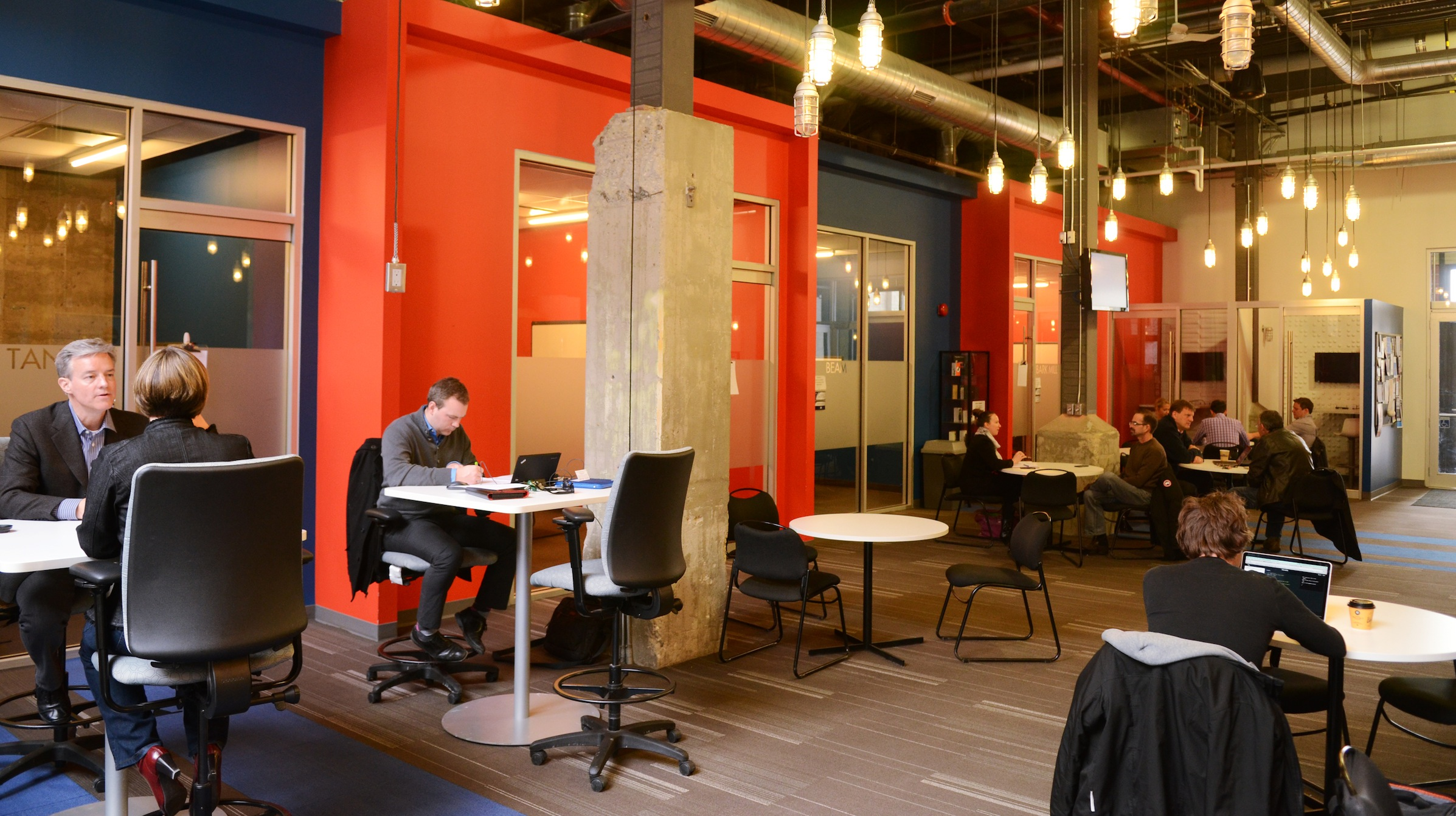 People huddle in discussion within Communitech in Kitchener's historic Tannery District in Kitchener, Ontario, March 18, 2014. Kitchener, historically the blue-collar twin to the university city of Waterloo, is today home to chic offices such as the Communitech building - a converted brick structure in the the historic Tannery District, adorned with modern art, which acts as an unofficial clubhouse for many small tech companies. Picture taken March 18, 2014.  REUTERS/Euan Rocha  (CANADA - Tags: EDUCATION SCIENCE TECHNOLOGY BUSINESS) - RTR3LJYJ