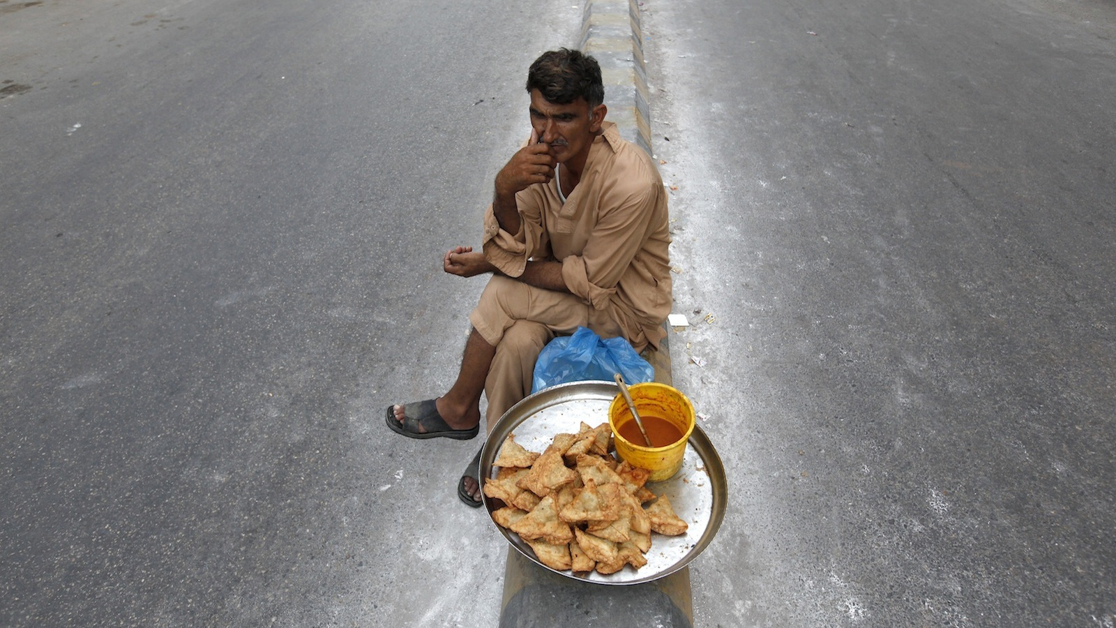 A man waits for customers while selling 'samosas', a traditional snack, along a road divider in Karachi April 20, 2014.
