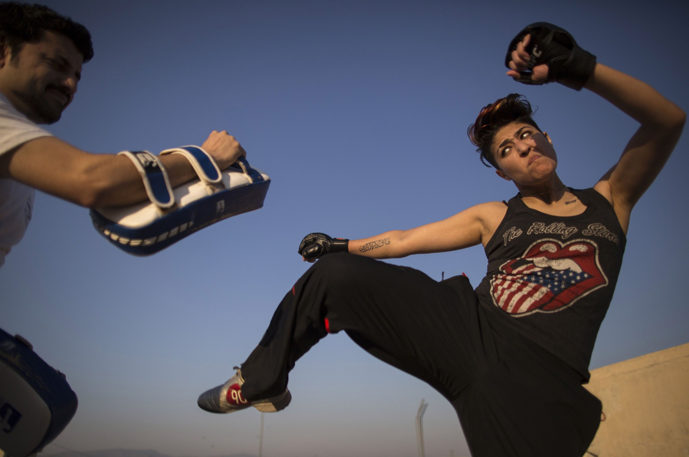 Interior designer Zahra Afridi (R) kicks a punching bag during a kickboxing training session at her home in Islamabad February 10, 2014. Afridi runs her own interior design company. Her most recent project was a Classic Rock Coffee cafe in Islamabad.