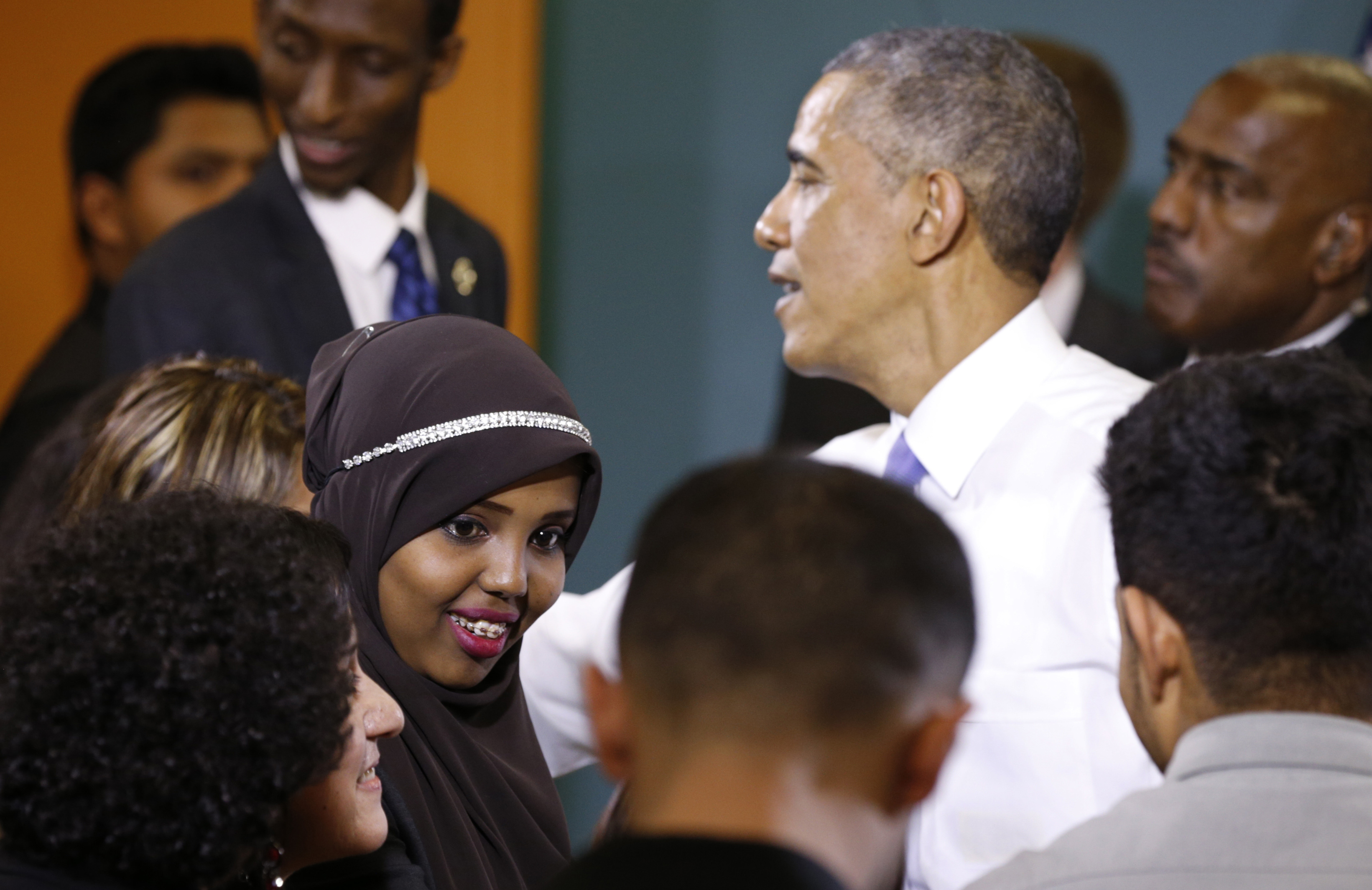 Hibo Omar, 17, a Nashville resident from Somalia, talks to her friends after greeting U.S. President Barack Obama (R) during his visit to Casa Azafran in Nashville, Tennessee December 9, 2014.  Obama visited Casa Azafran to speak about immigration reform. Casa Azafran is a community center and home to a number of immigrant-related nonprofits.  REUTERS/Kevin Lamarque  (UNITED STATES - Tags: POLITICS SOCIETY IMMIGRATION) - RTR4HCZN