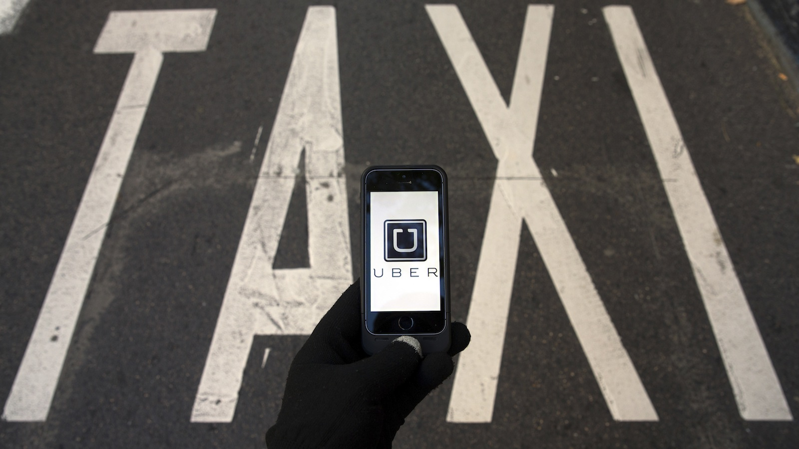 The logo of car-sharing service app Uber on a smartphone over a reserved lane for taxis in a street is seen in this photo illustration taken in Madrid on December 10, 2014. A Madrid judge has ordered U.S.-based online car booking company Uber to cease operations in Spain, the latest ban on the popular service. Taxi drivers around the world consider Uber unfairly bypasses local licensing and safety regulations by using the internet to put drivers in touch with passengers. REUTERS/Sergio Perez