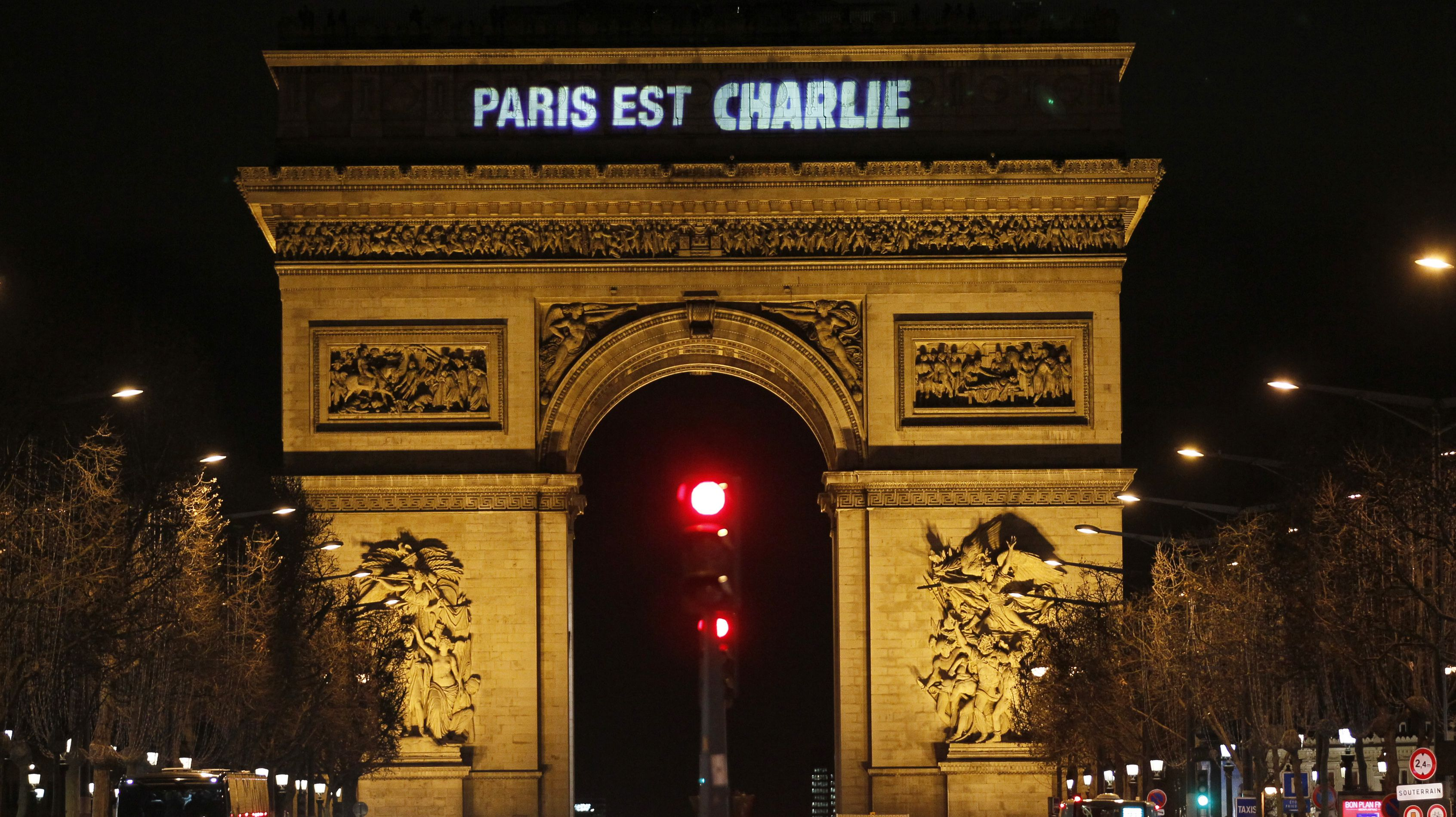 """The message """"Paris is Charlie"""" is projected on the Arc de Triomphe in Paris January 9, 2015, in tribute to the victims following Wednesday's deadly attack at the Paris offices of weekly satirical newspaper Charlie Hebdo by two masked gunmen who shouted Islamist slogans. REUTERS/Youssef Boudlal (FRANCE - Tags: CRIME LAW MEDIA) - RTR4KS0J"""