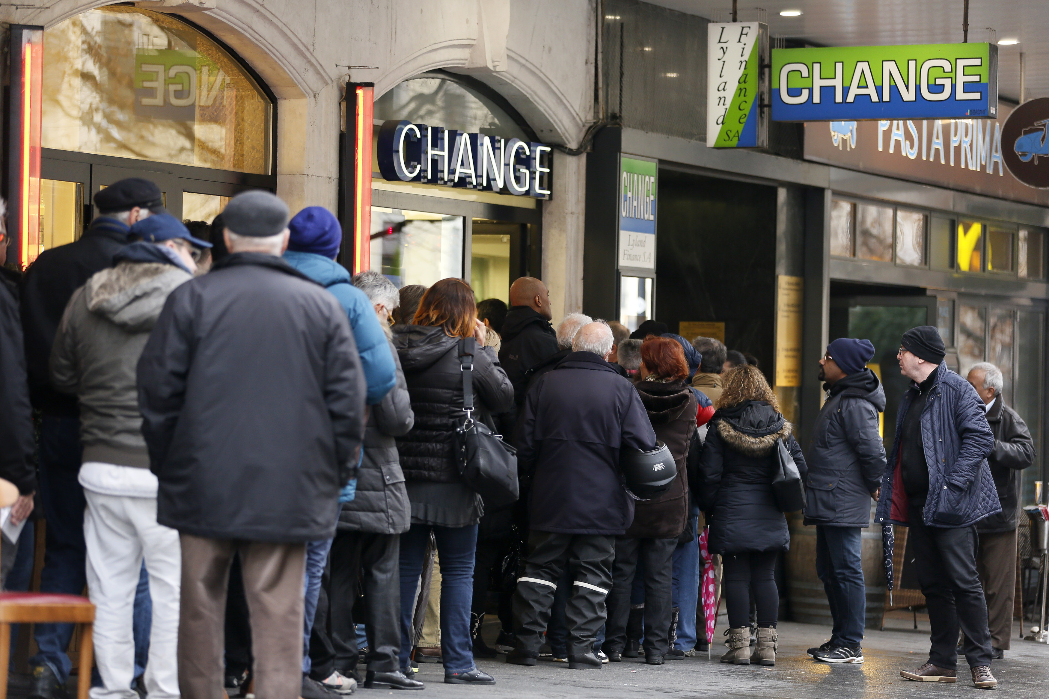 People queue outside a currency exchange office in Geneva, January 16, 2015. Swiss stocks sank on Friday, extending the sell-off sparked by the Swiss National Bank's surprise decision to remove a ceiling on the Swiss franc that sent the currency soaring. REUTERS/Pierre Albouy (SWITZERLAND  - Tags: BUSINESS POLITICS)   - RTR4LOLV