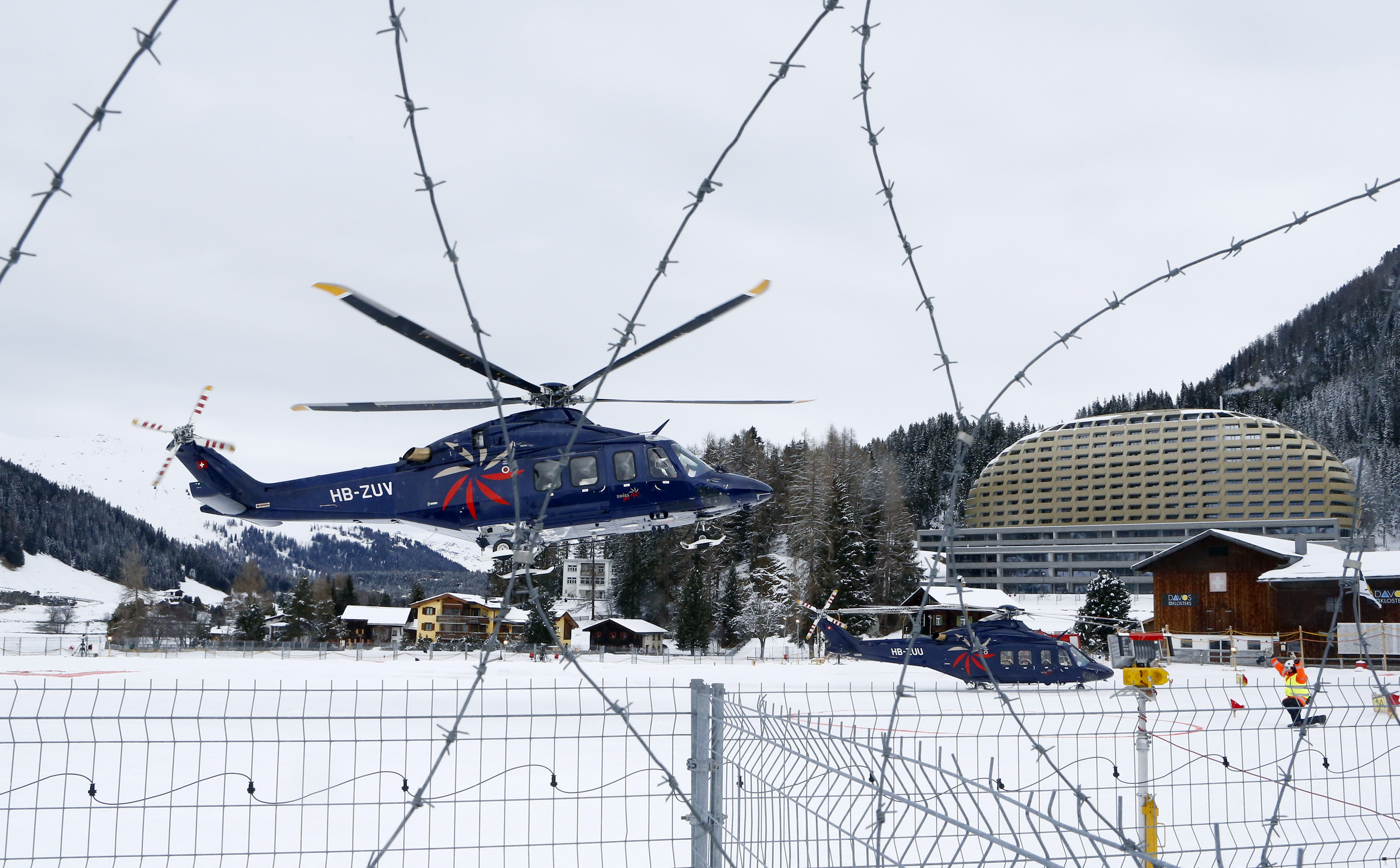 A participant arrives by private helicopter for the World Economic Forum (WEF)  in the Swiss mountain resort of Davos January 20, 2015. More than 1,500 business leaders and 40 heads of state or government will attend the January 21-24 meeting of the World Economic Forum (WEF) to network and discuss big themes, from the price of oil to the future of the Internet. This year they are meeting in the midst of upheaval, with security forces on heightened alert after attacks in Paris, the European Central Bank considering a radical government bond-buying programme and the safe-haven Swiss franc rocketing.    REUTERS/Ruben Sprich (SWITZERLAND  - Tags: POLITICS BUSINESS)   - RTR4M517
