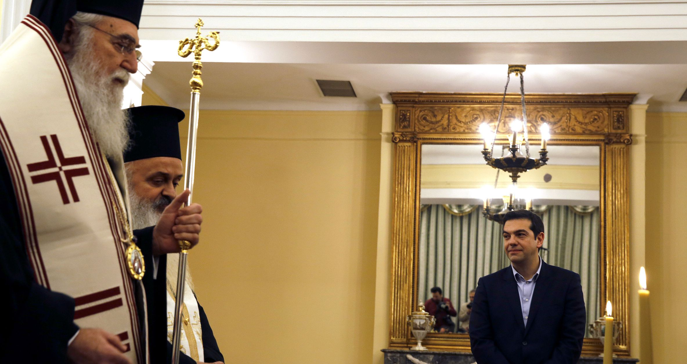 Greek orthodox priests conduct a swearing in ceremony for Greece's new government as newly appointed Greek Prime Minister and winner of the Greek parliamentary elections Alexis Tsipras looks on at the presidential palace in Athens January 27, 2015.  REUTERS/Yannis Behrakis (GREECE - Tags: POLITICS ELECTIONS) - RTR4N71S