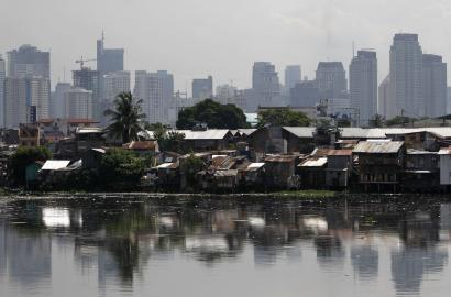 High-rise buildings are seen in the background with slum dwellings in the front, near a polluted river in Manila May 31, 2013. The Philippines.