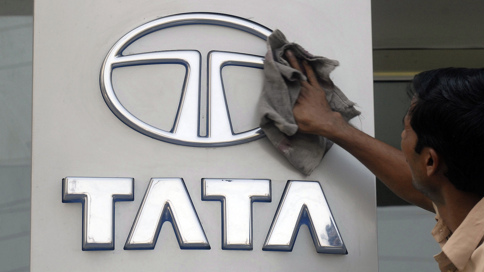 A worker cleans a Tata Motors logo outside its showroom in the southern Indian city of Hyderabad October 26, 2009. Tata Motors Ltd, India's largest vehicle maker, reported a sharp jump in quarterly net profit, beating forecasts, on improved margins from lower input prices, recovery in volumes and aided by lower foreign exchange losses.