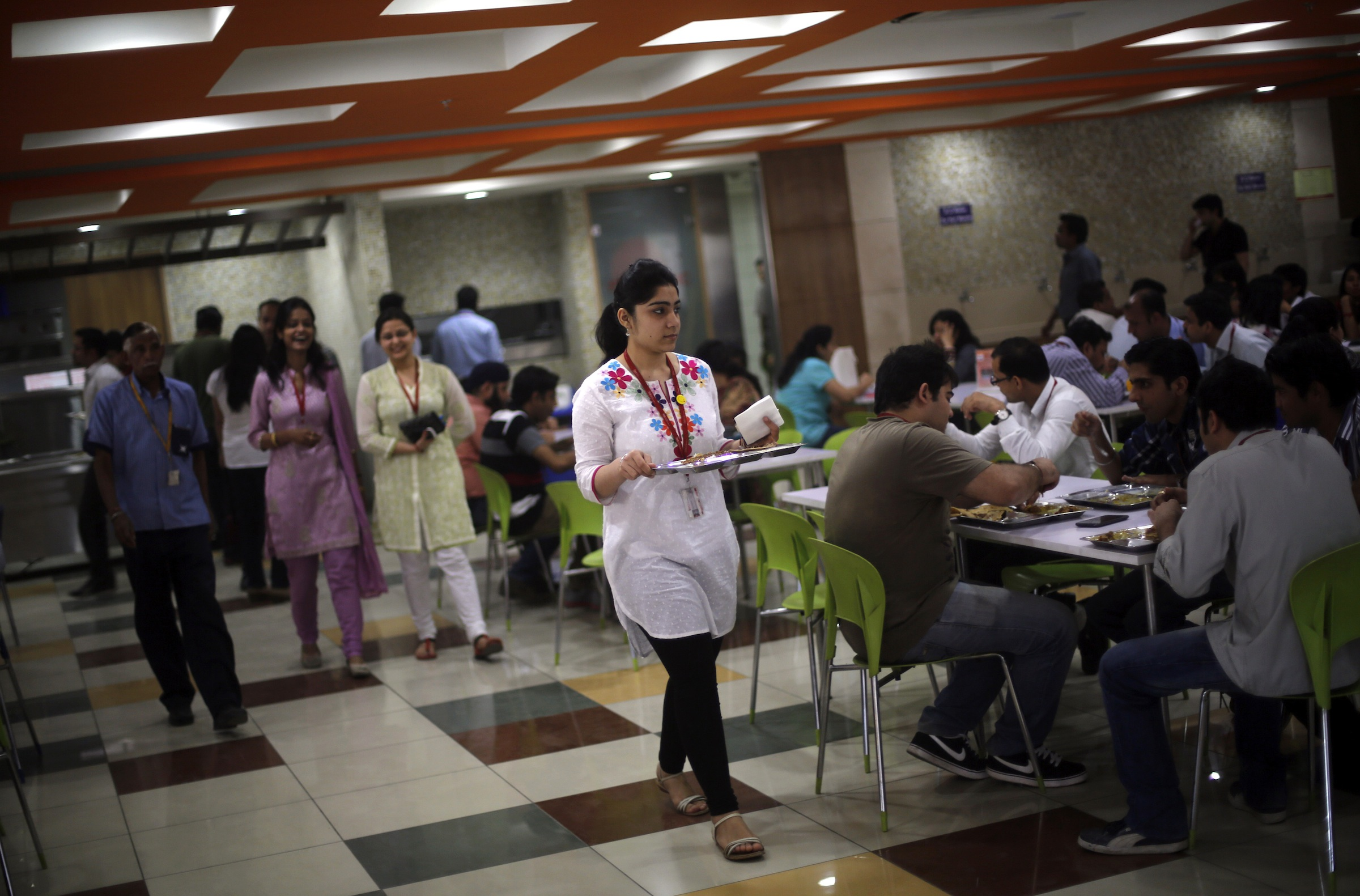 """An employee carries her lunch at a cafeteria inside Tech Mahindra office building in Noida on the outskirts of New Delhi March 18, 2013. India's IT outsourcers are promoting """"mini CEOs"""" capable of running businesses on their own, while trimming down on the hordes of entry-level computer coders they normally hire as they try to squeeze more profits out of their staff. To match Analysis INDIA-TECH/STAFFING  Picture taken March 18, 2013.   REUTERS/Adnan Abidi (INDIA - Tags: BUSINESS SCIENCE TECHNOLOGY EMPLOYMENT) - RTXXW8O"""