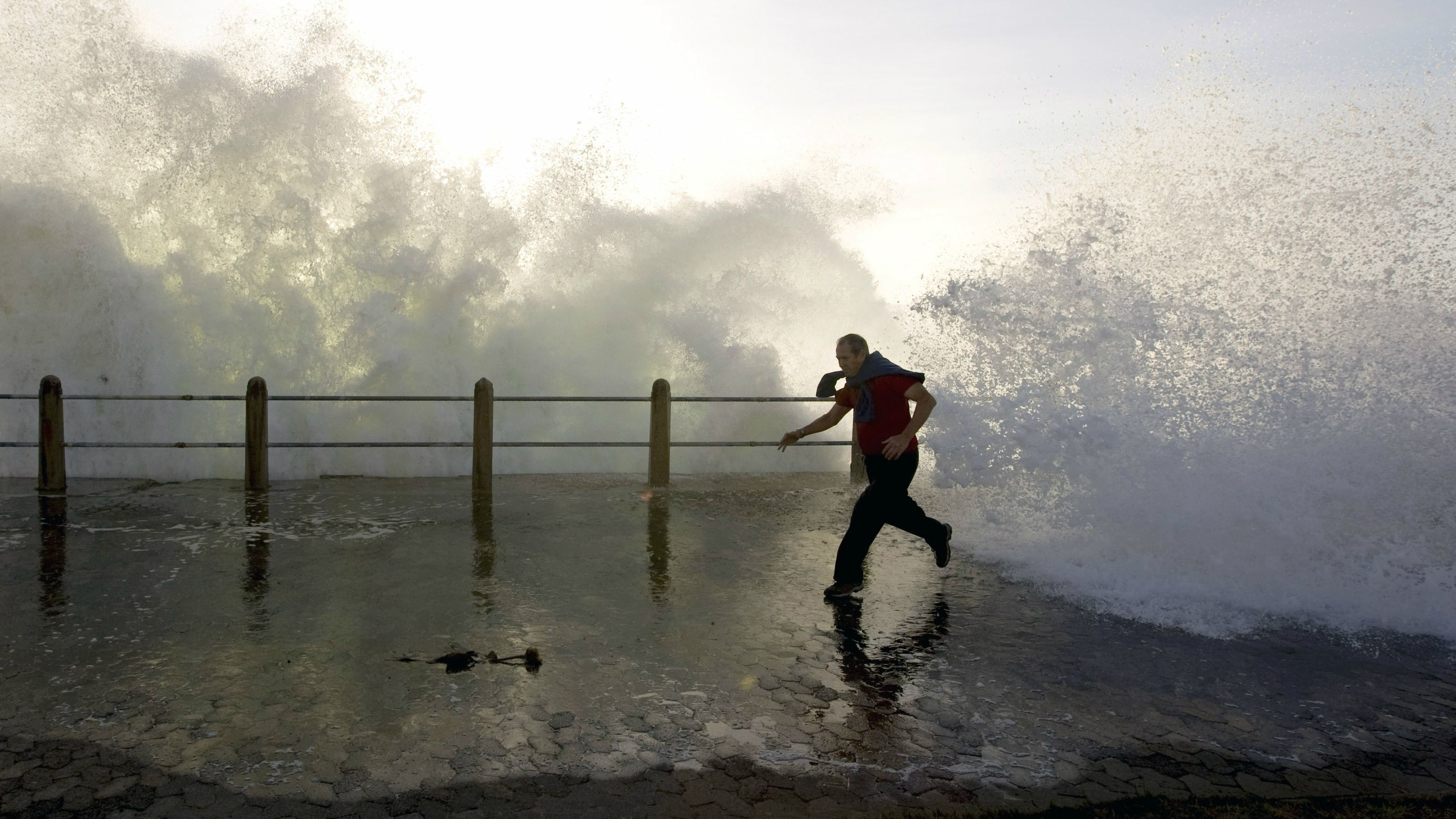 A man runs as heavy waves crash along the Sea Point beachfront in Cape Town, May 5, 2008. Waves of up to six metres are expected, driven by seasonal winter swells. REUTERS/Mike Hutchings