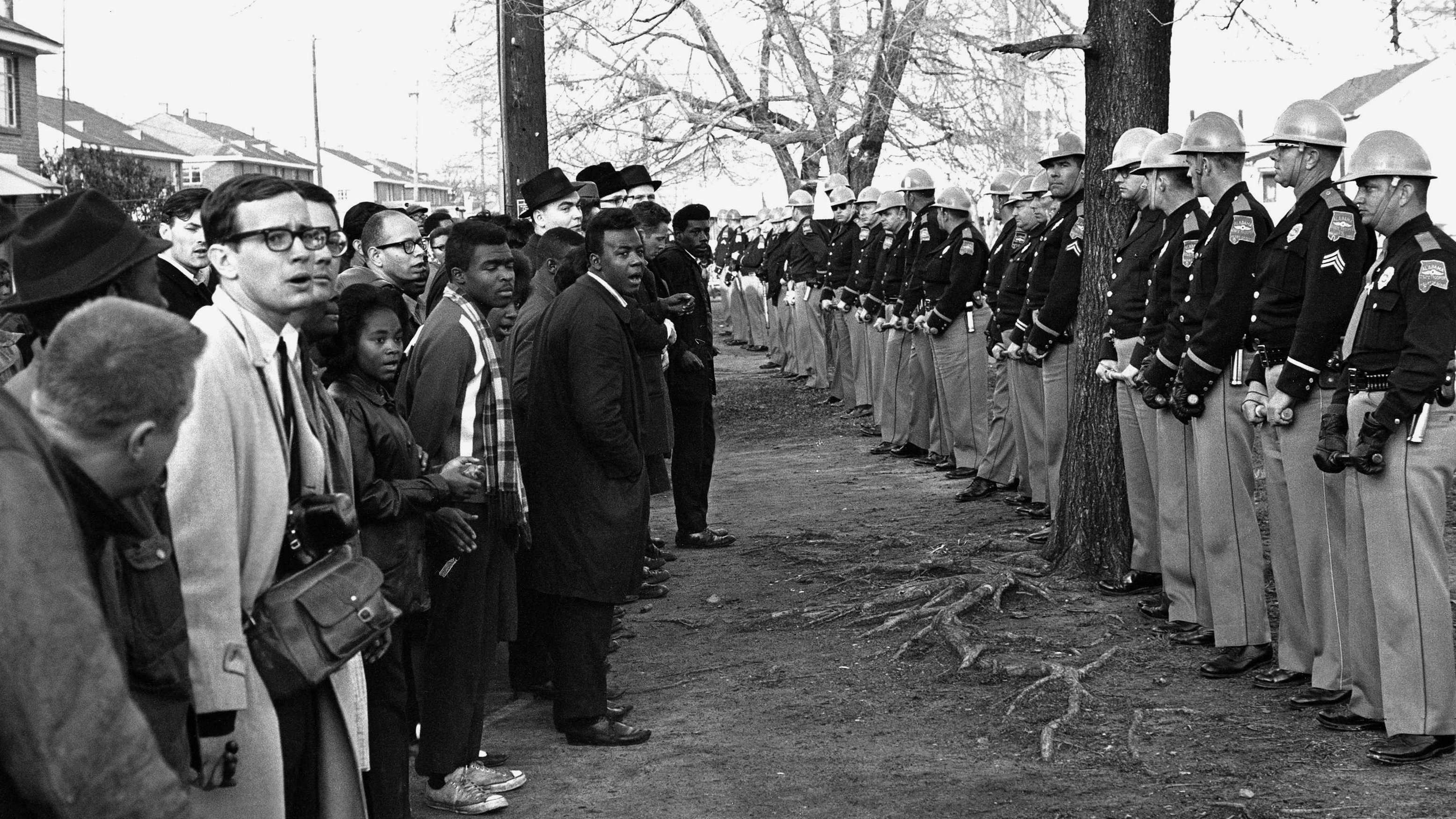 A policemen hold back demonstrators, who started off in all directions, in an attempt to march to the court house, March 13, 1965, Selma, Ala. Police kept the demonstrators hemmed up in a square block area where they have attempted several times break through.