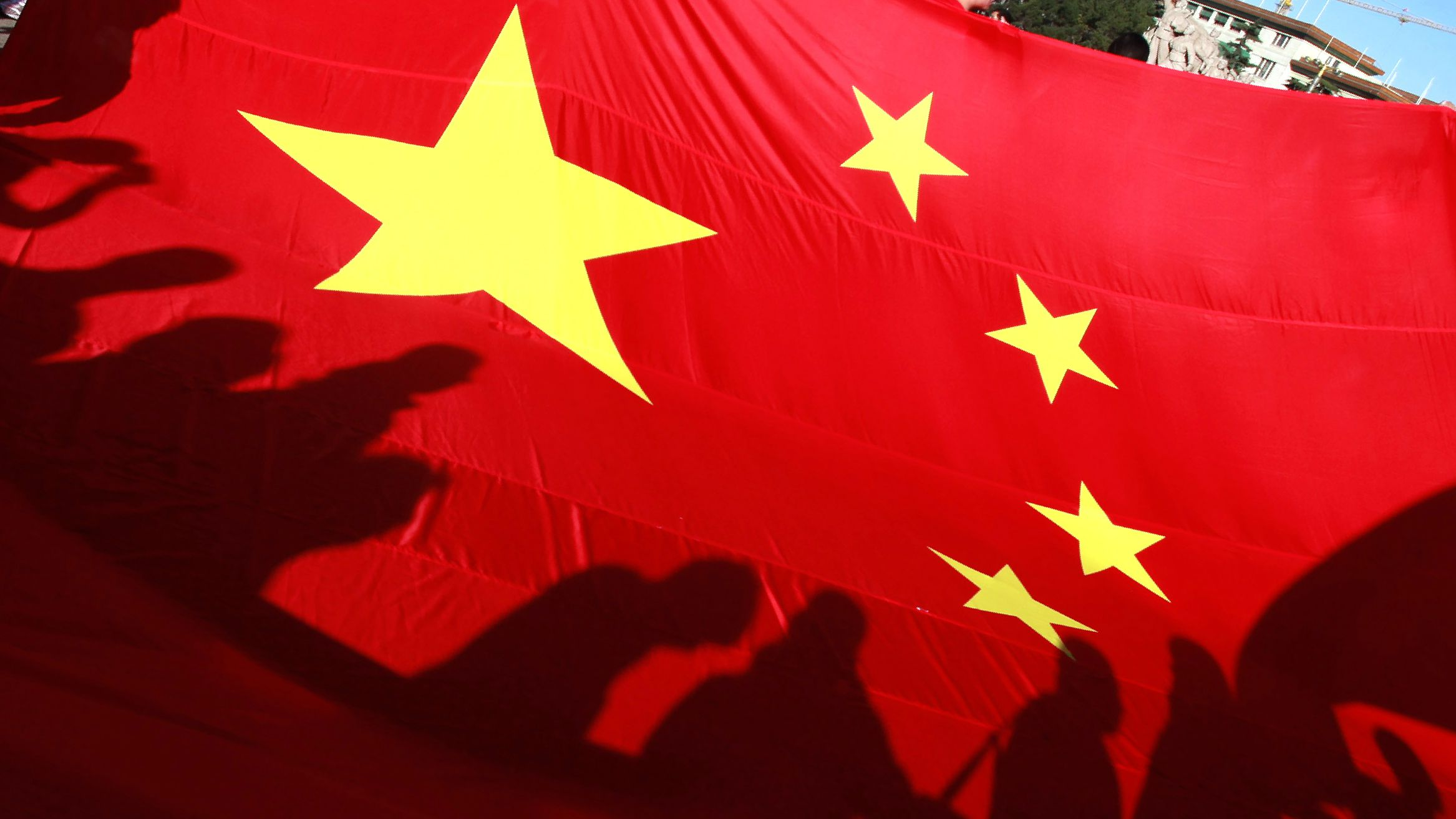 Participants cast shadows on a giant Chinese national flag before the start of the Beijing Marathon on Tiananmen Square in Beijing Sunday, Oct. 16, 2011. (AP Photo/Ng Han Guan