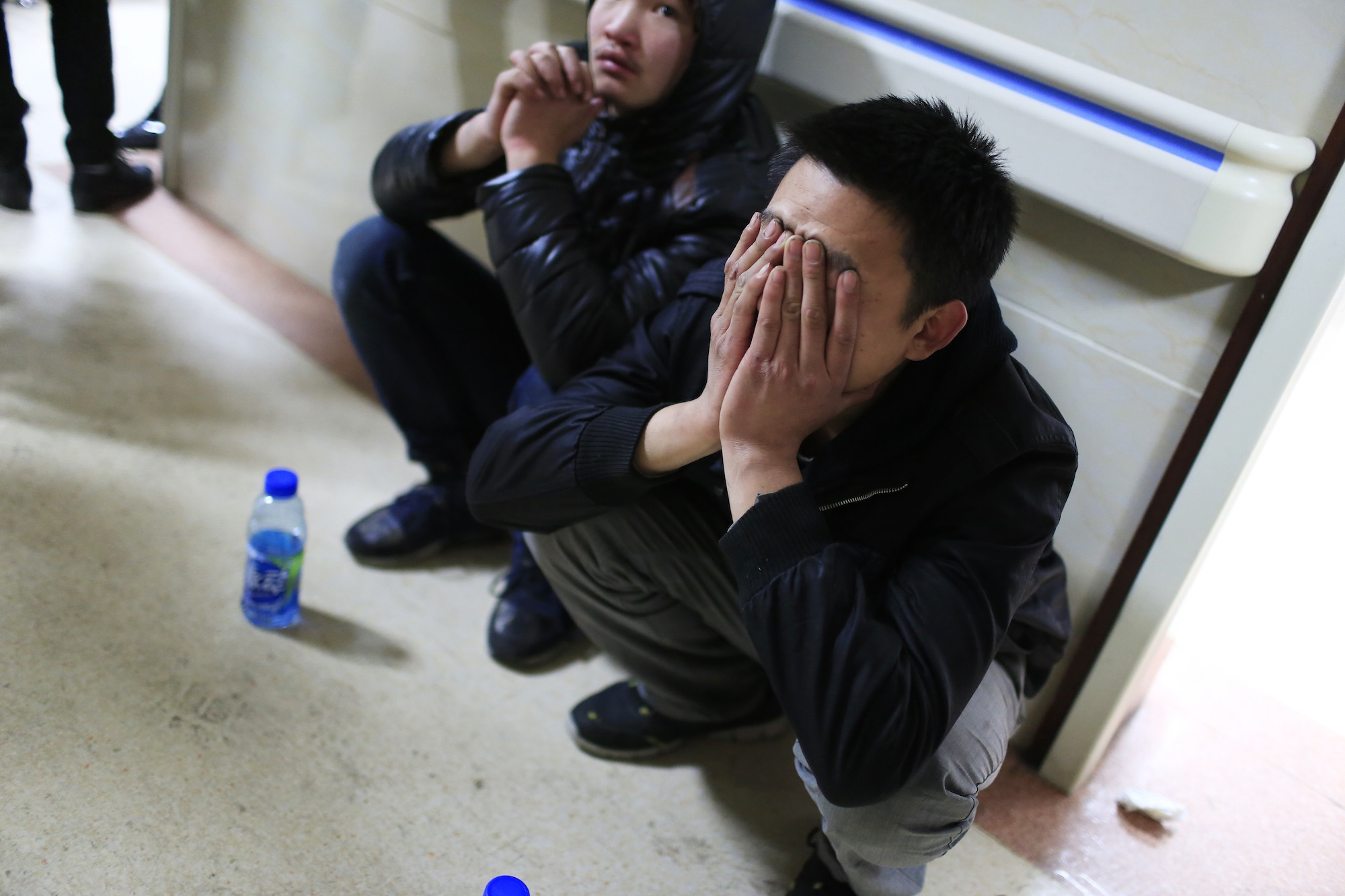 A friend of a victim covers his face as he waits outside a hospital where injured people of a stampede incident are treated, in Shanghai