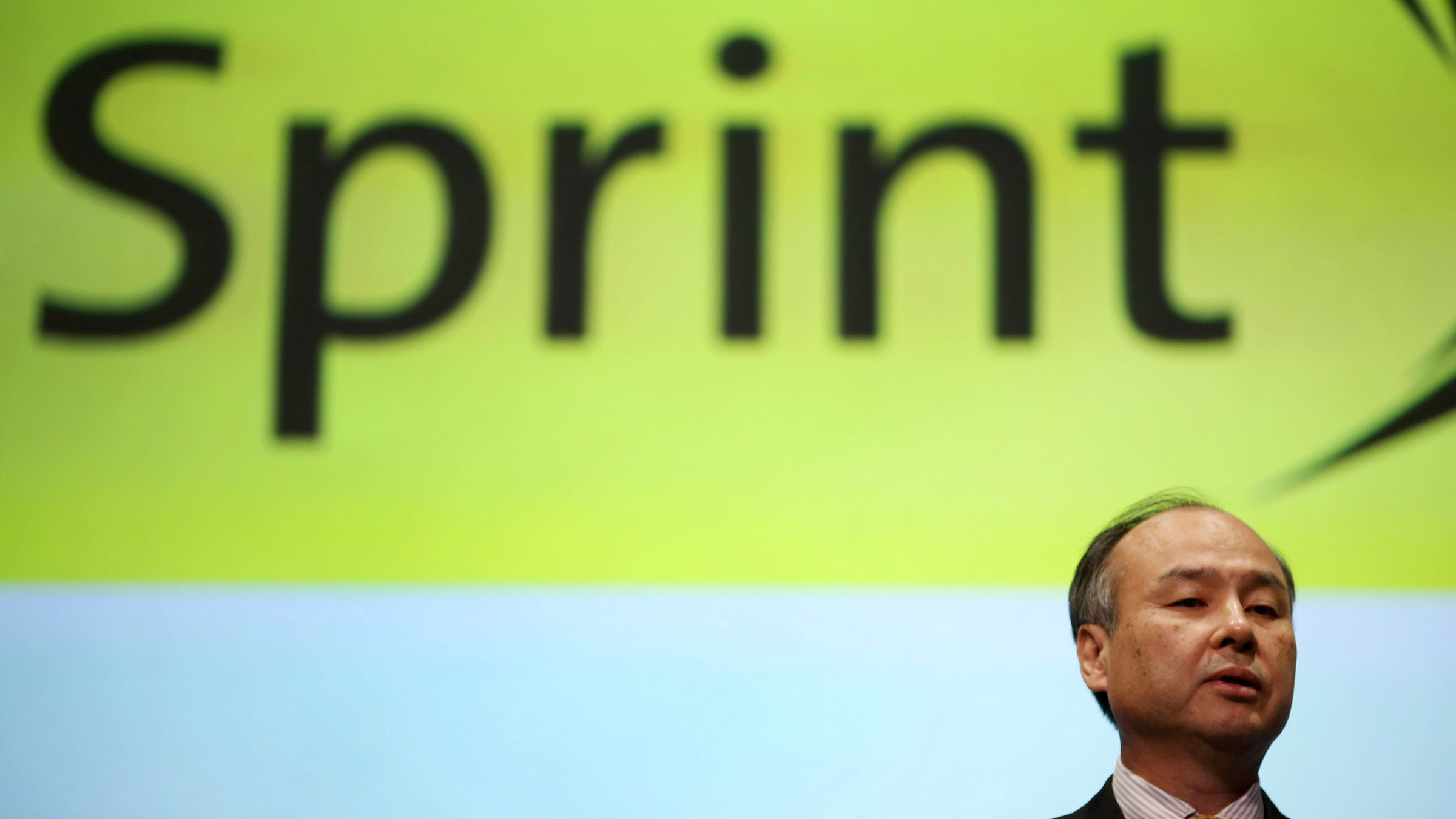 Softbank founder and chief executive Masayoshi Son speaks in front of a logo of U.S. telecom company Sprint  during a news conference in Tokyo, Tuesday, Nov. 4, 2014. Softbank's quarterly profit nearly tripled as gains from the IPO of Chinese e-commerce company Alibaba offset losses at U.S. mobile carrier Sprint. ()