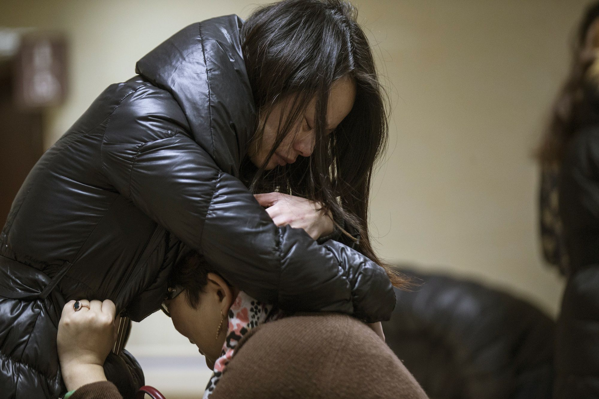 Relatives of a victim hug as they wait at a hospital where injured people of a stampede incident are treated.