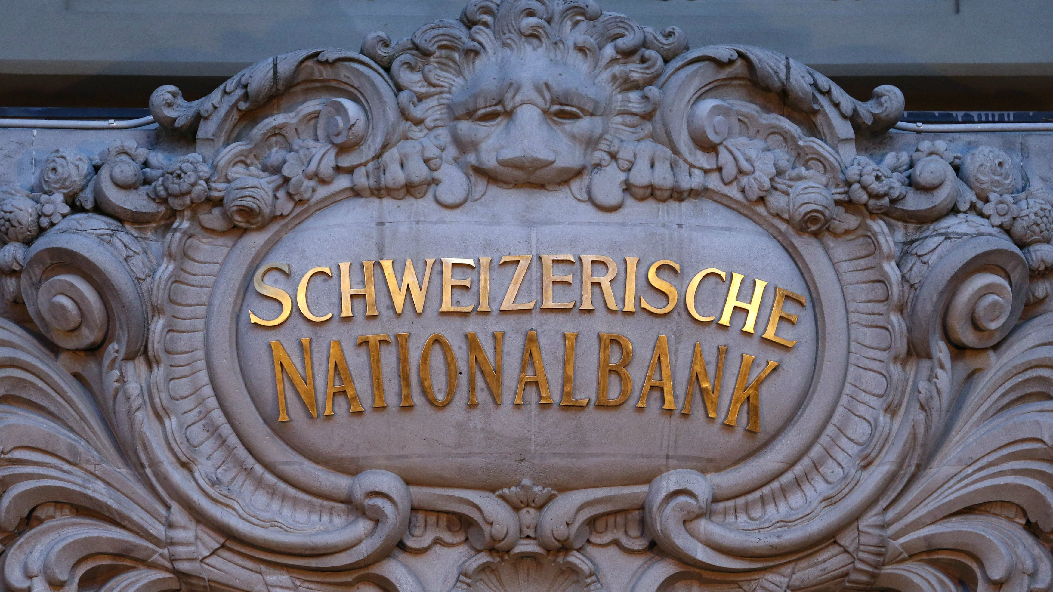 The logo of the Swiss National Bank (SNB) is seen at the entrance of the SNB in Bern January 15, 2015. The SNB shocked financial markets on Thursday by scrapping a three-year-old cap on the franc, sending the safe-haven currency soaring against the euro and stocks plunging amid fears for the export-reliant Swiss economy. REUTERS/Thomas Hodel (SWITZERLAND - Tags: BUSINESS POLITICS LOGO)
