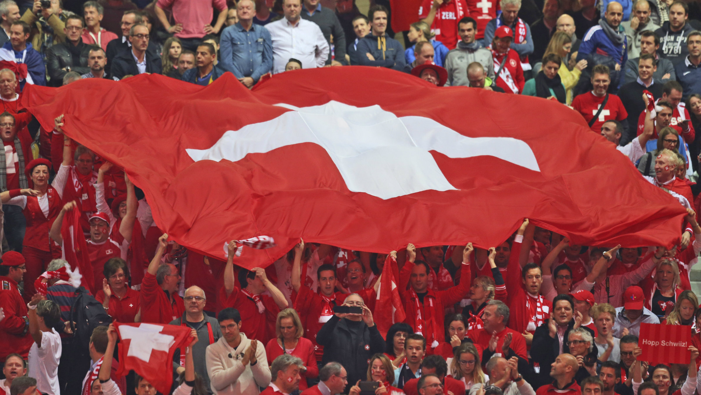 Swiss fans hold the national flag as Roger Federer defeats France's Richard Gasquet to win the Davis Cup final between France and Switzerland at Stade Pierre Mauroy in Lille, northern France, Sunday, Nov. 23, 2014. (AP Photo/Peter Dejong)