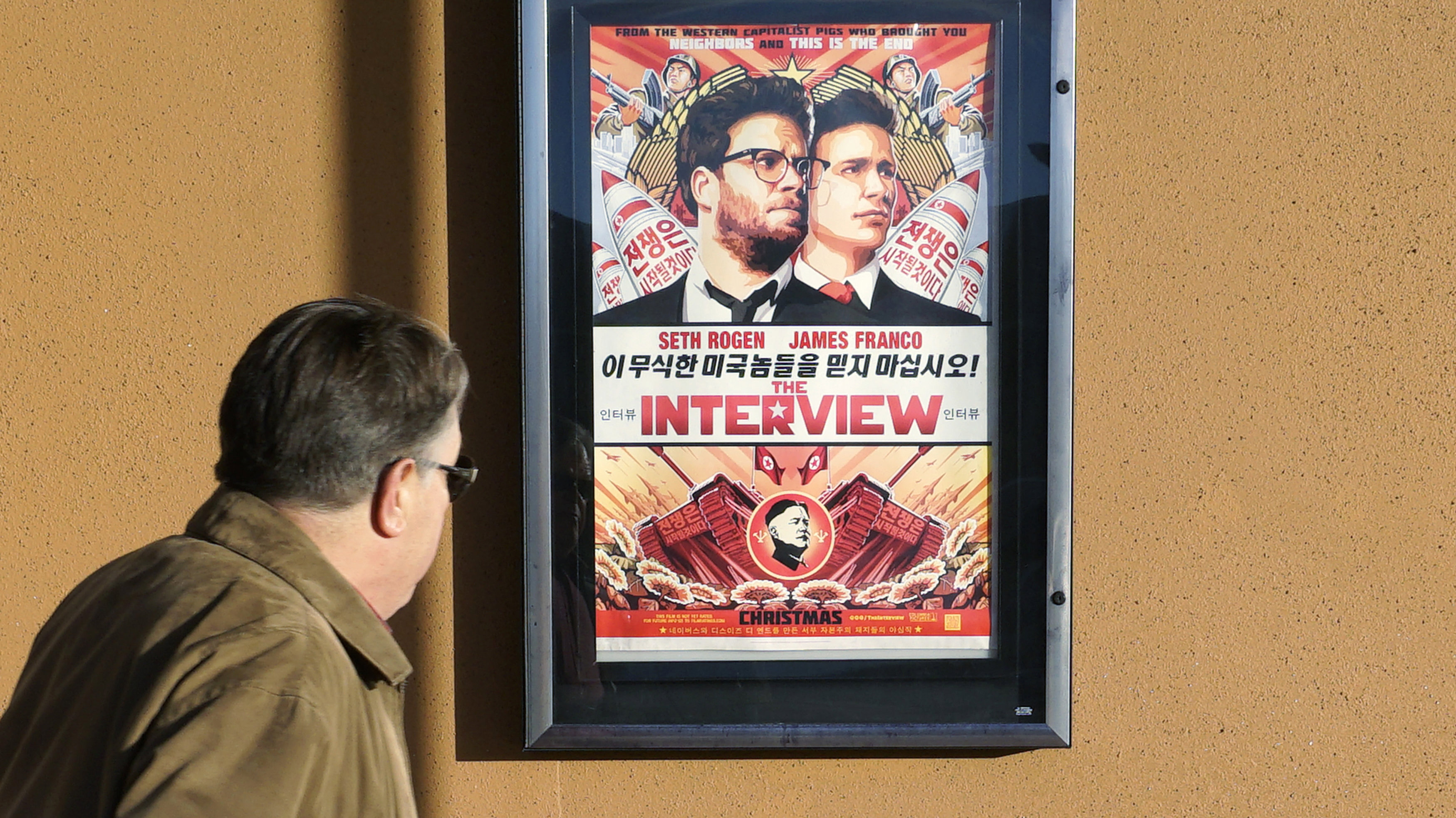 """A man walks by the poster for the film """"The Interview"""" outside the Alamo Drafthouse theater in Littleton, Colorado December 23, 2014. Sony Pictures said on Tuesday it will release """"The Interview"""" to a limited number of theatres on December 25, less than a week after it cancelled the comedy's release following a devastating cyberattack blamed on North Korea. Sony's about-face came after it absorbed withering criticism, even from President Barack Obama for its decision last week to pull the film, which was seen not only as self-censorship in Hollywood but also caving into hackers working for North Korea."""