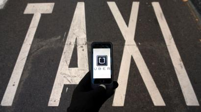 The logo of car-sharing service app Uber on a smartphone over a reserved lane for taxis in a street is seen in this photo illustration taken in Madrid on December 10, 2014. A Madrid judge has ordered U.S.-based online car booking company Uber to cease operations in Spain, the latest ban on the popular service. Taxi drivers around the world consider Uber unfairly bypasses local licensing and safety regulations by using the internet to put drivers in touch with passengers.