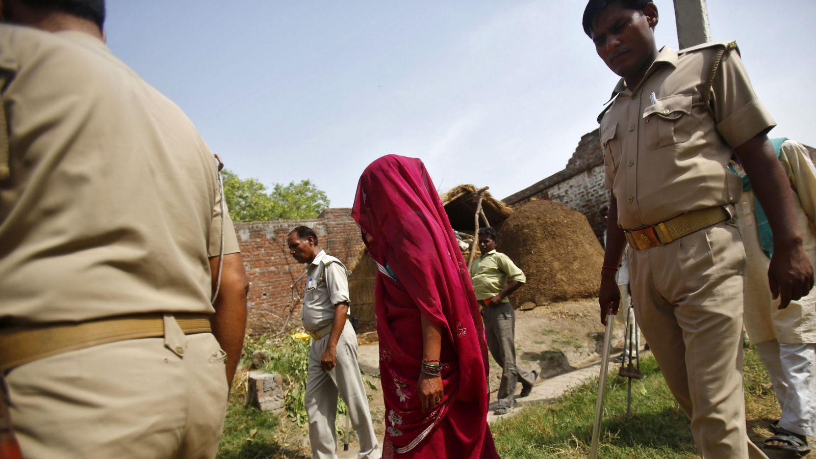 The veiled mother of one of the two teenage girls, who were raped and hanged from a tree, walks along with policemen at Budaun district in the northern Indian state of Uttar Pradesh May 31, 2014. India's new Home Minister Rajnath Singh weighed in on Friday in a grisly case in which two teenage girls were raped and hanged from a tree this week in Uttar Pradesh, as public anger and political controversy over the attack gain momentum.