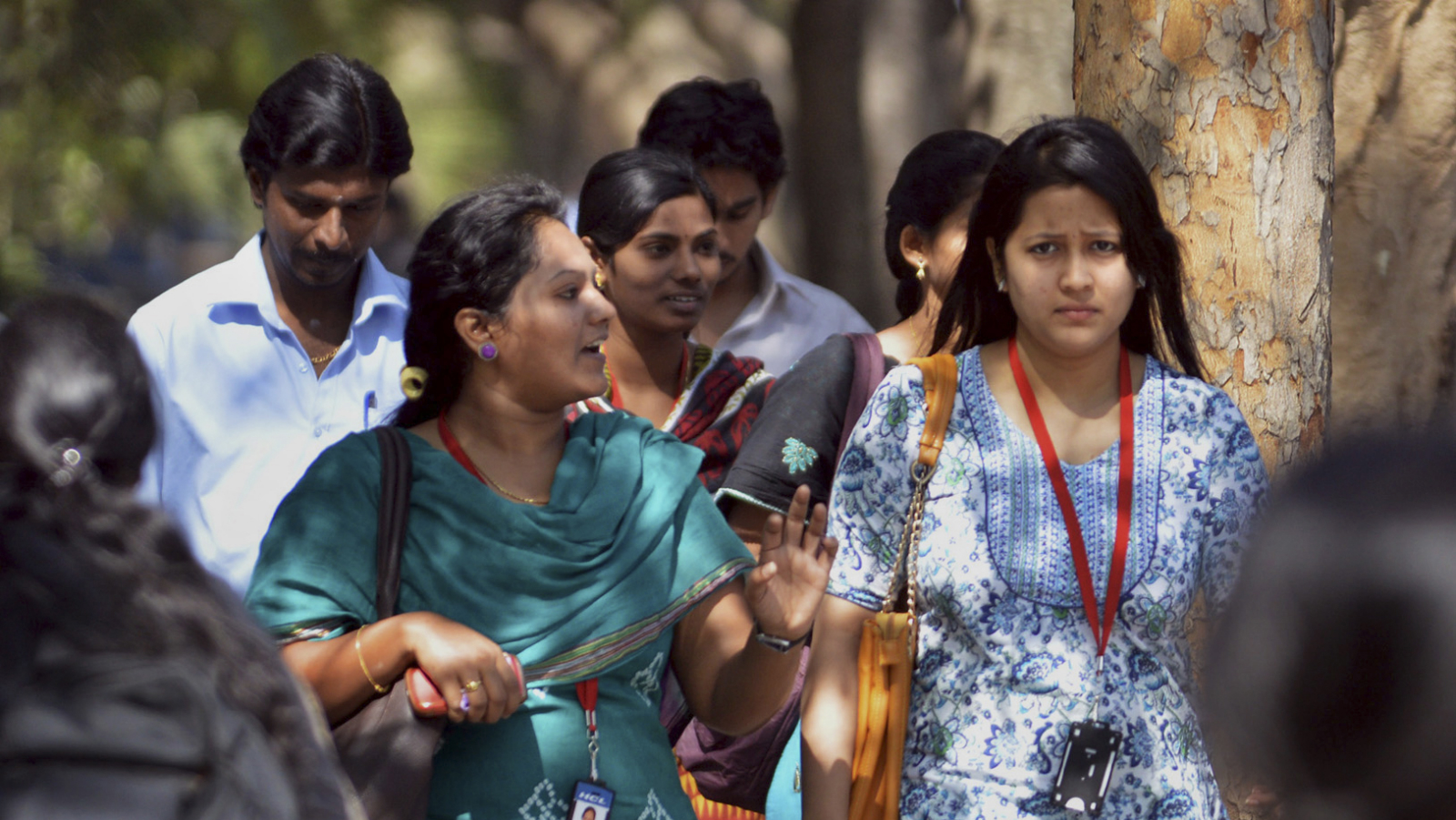 In this Wednesday, March 26, 2014 photo, young Indian employees of Infosys Technologies walk outside the company's headquarters at Electronic City in Bangalore, India. As the world's largest democracy of 1.2 billion people, including 814 million voters, launches a marathon six-week national election contest, all eyes are on India's enormous population of ambitious, tech-savvy and politically engaged youths. Nowhere is the high-tech transition more clear than amid the bright cafes and technology companies of Bangalore, seen as the economy's beating heart and brain trust with its large number of scientists, engineers and corporate professionals drawn from India's brightest youths. With 63 percent of its population under 25, Bangalore is one of India's youngest cities.