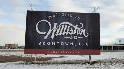 """A sign reads """"Welcome to Williston ND Boomtown USA"""" along the main road in Williston, North Dakota November 12, 2014."""