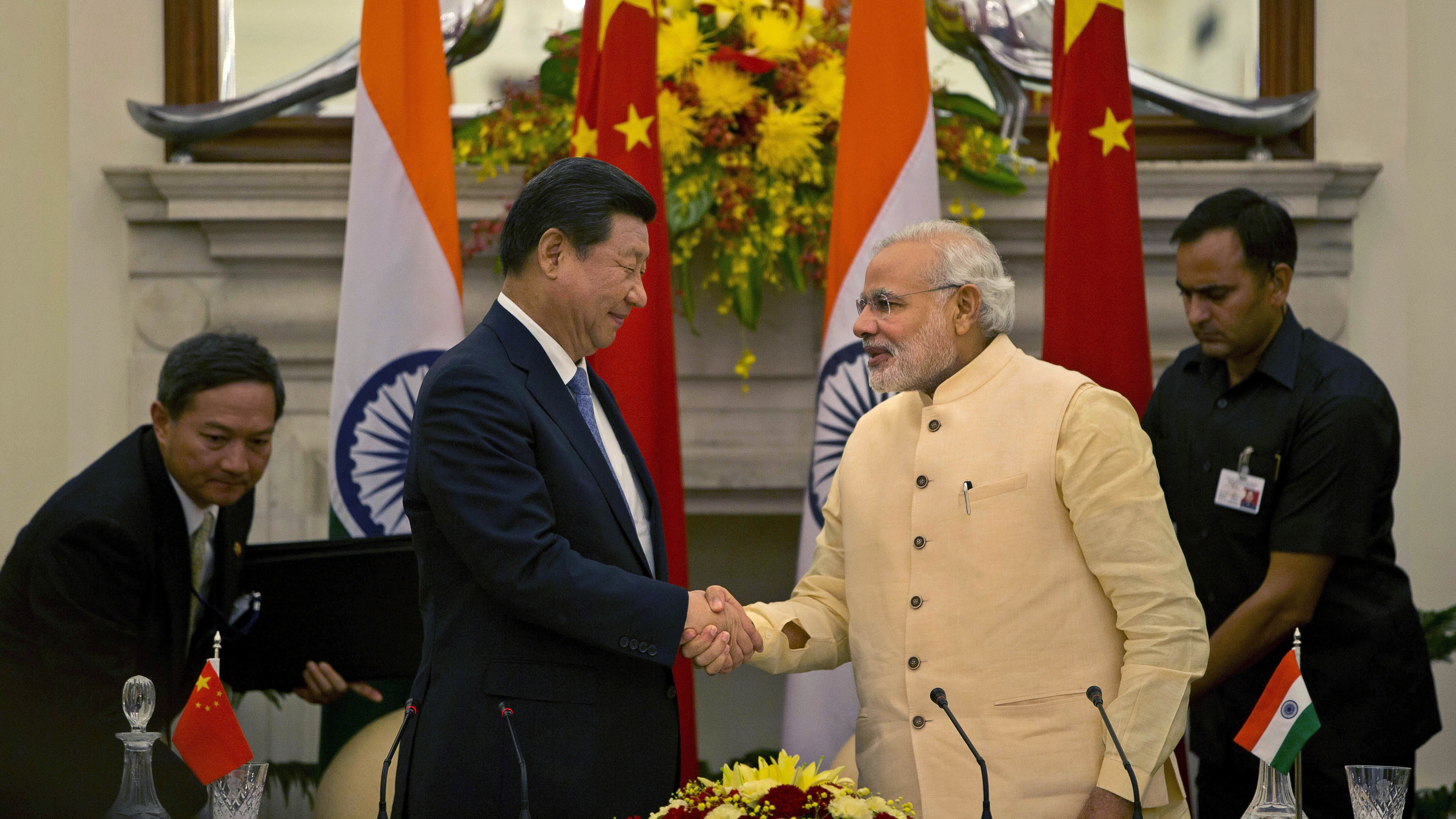 Chinese President Xi Jinping shakes hands with Indian Prime Minister Narendra Modi, right after signing agreements in New Delhi, India, Thursday, Sept. 18, 2014. Xi vowed to bring prosperity to Asia and create opportunities for the world as he and Modi began talks Thursday to deepen cooperation through investment and trade. (AP Photo /Manish Swarup)