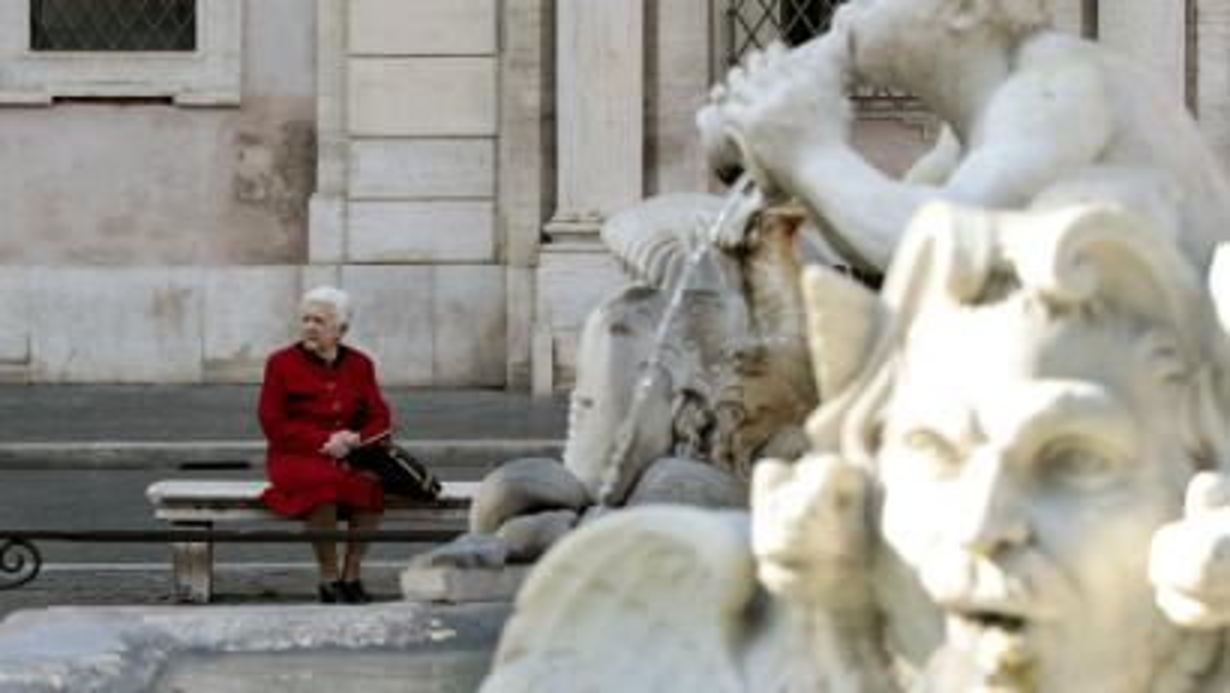 A woman sits near Piazza Navona's Fontana del Moro in Rome.