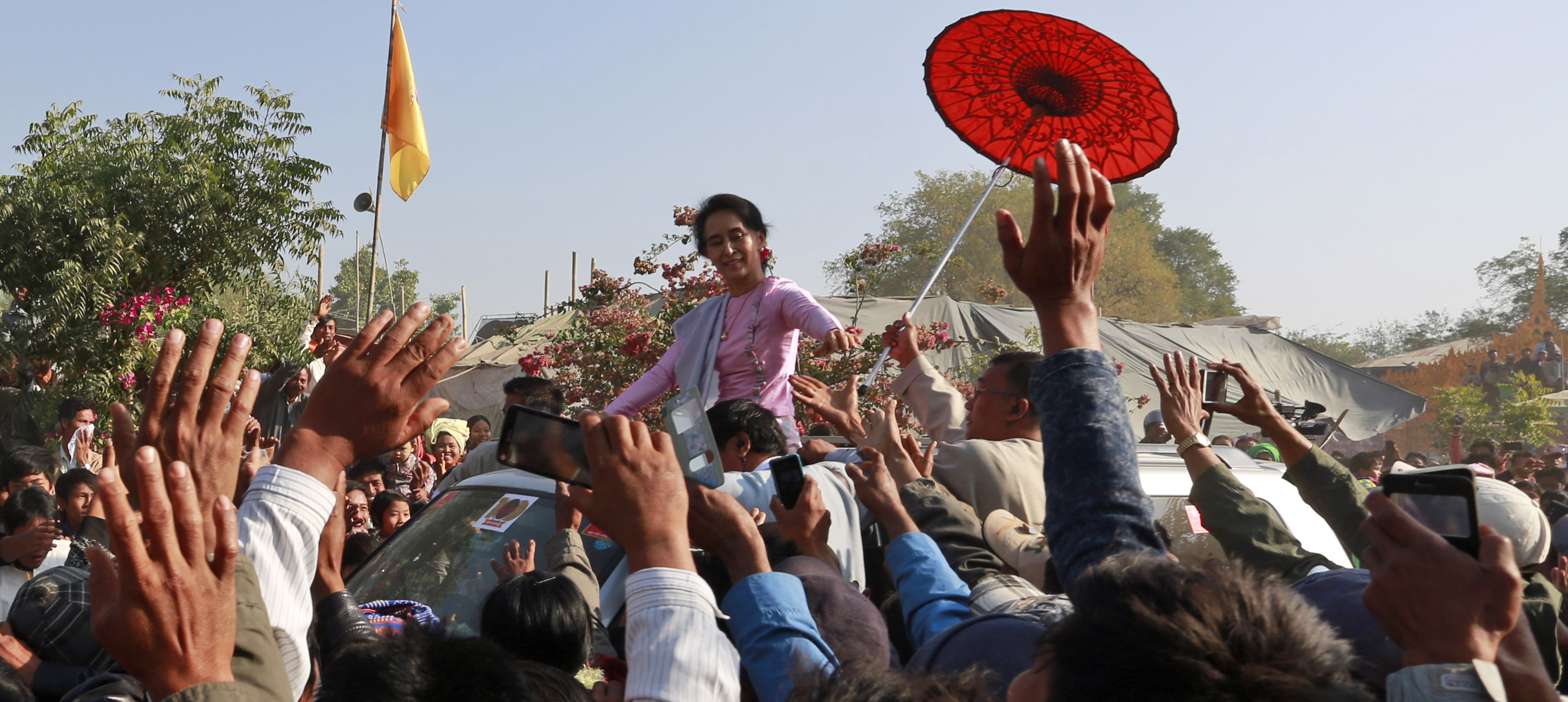 Myanmar Opposition Leader Aung San Suu Kyi greets supporters from vehicle as she leaves a ceremony to mark the 100th birthday anniversary of her late father, Gen. Aung San, at Nat Mauk township, native place of her father, Magwe Division, central Myanmar, Friday, Feb.13, 2015. Commemorations are held all across the country to celebrate the 100th year birth anniversary of the late independence hero Gen. Aung San, father of Myanmar's democracy icon Aung San Suu Kyi. Photography and painting exhibitions, performances and fairs are being held for several days to mark the 100-year birthday of Aung San.   (AP Photo/Khin Maung Win)