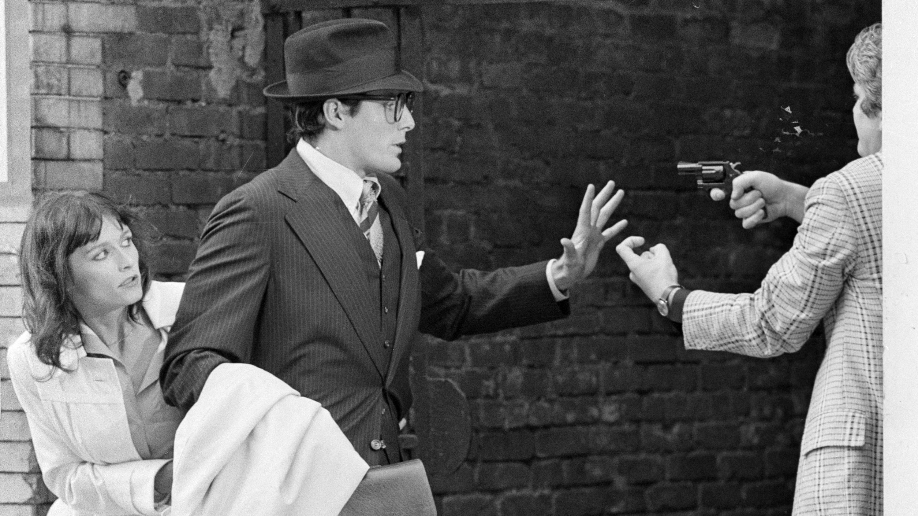 """Clark Kent, aka Superman portrayed by Christopher Reeve, raises his hand as he and Lois Lane, portrayed by Margot Kidder, left, are mugged by an armed man in an alleyway in the Lower East Side during a scene from """"Superman"""" filmed in New York City, Friday, July 8, 1977. (AP Photo)"""