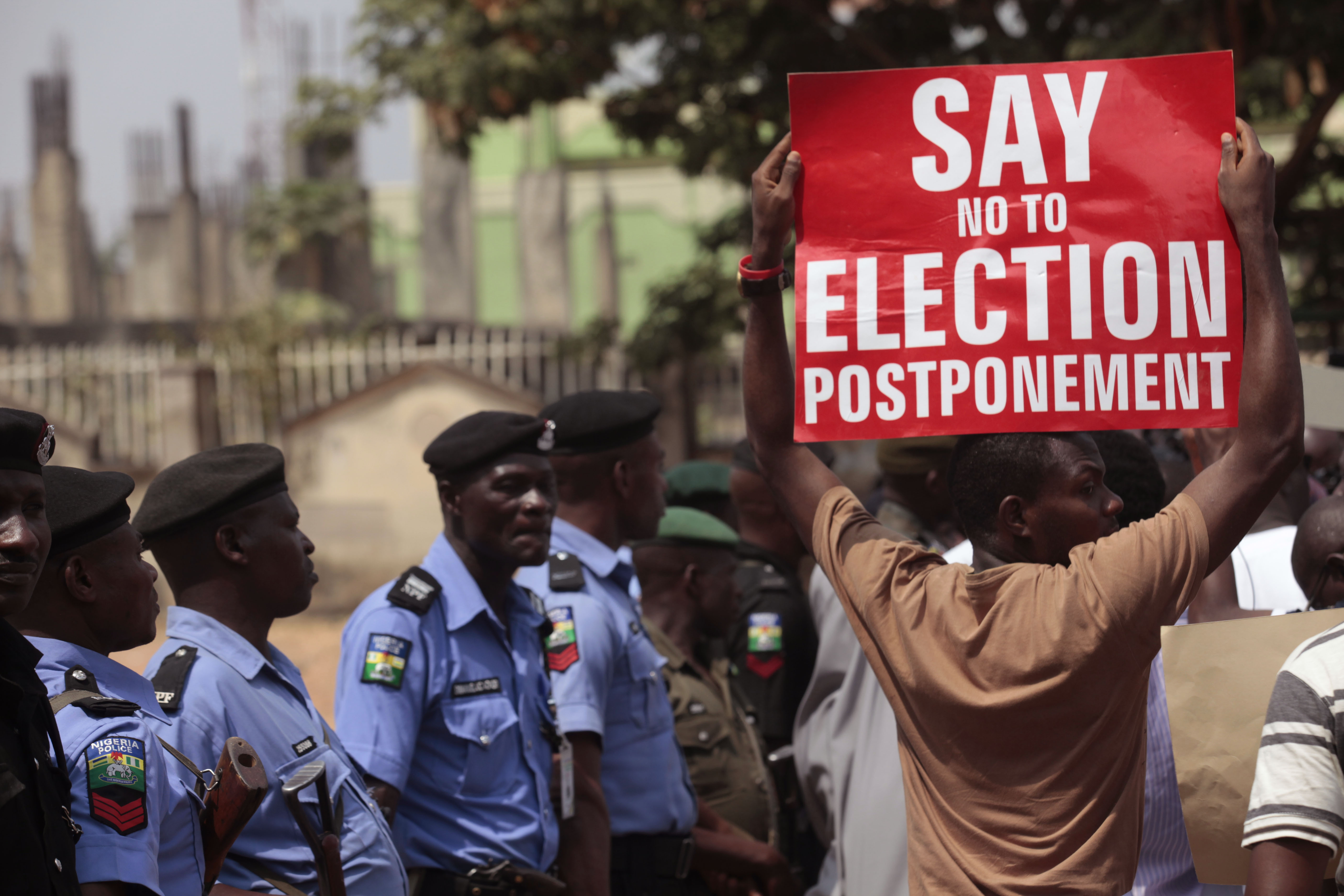 a protestor holds a banner as Nigerian security forces look on