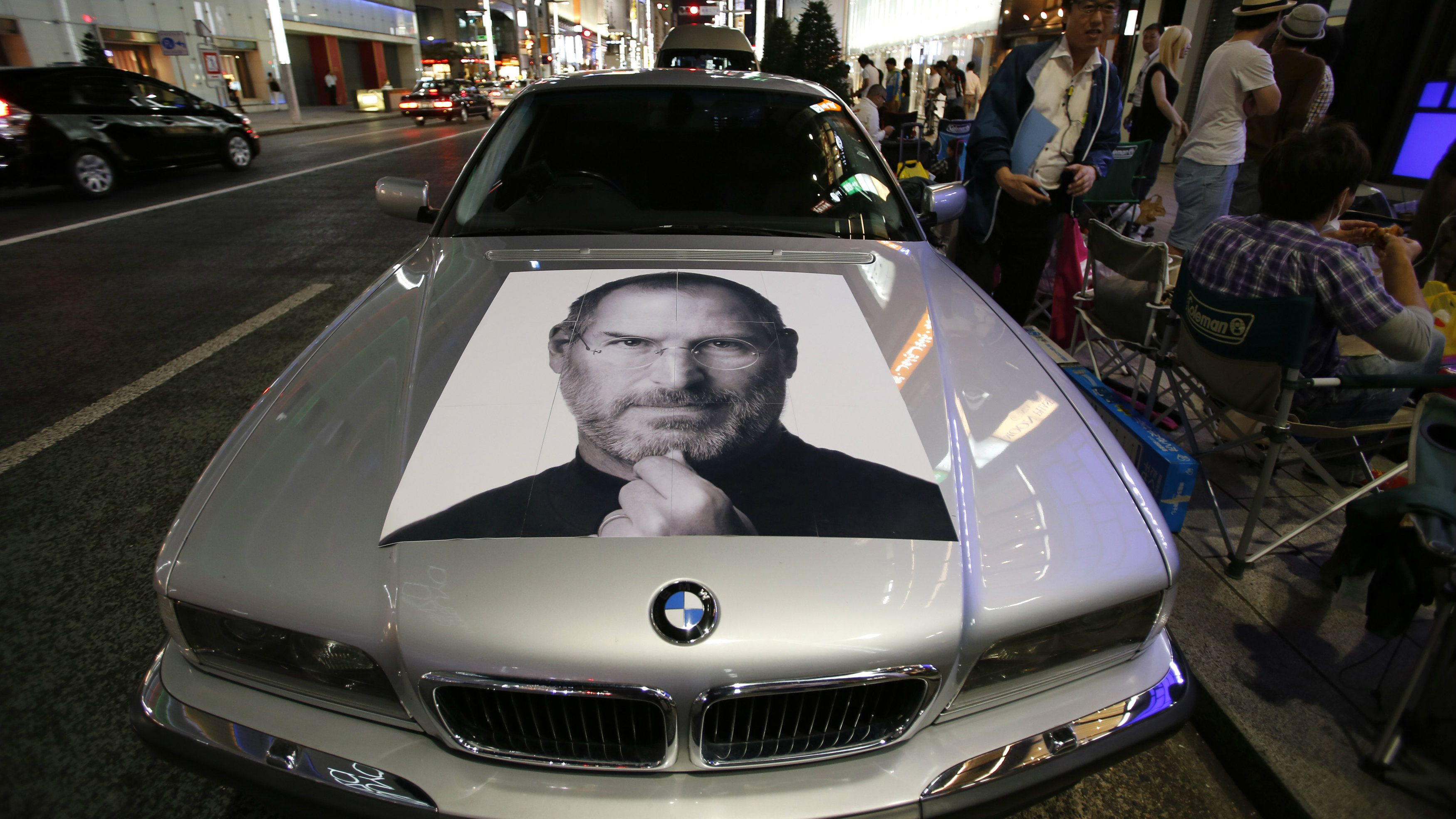 A portrait of Apple's co-founder Steve Jobs is seen on a BMW car as people wait for the release of Apple's new iPhone 5S and 5C, near the Apple Store at Tokyo's Ginza shopping district September 19, 2013, a day before the phones go on sale.