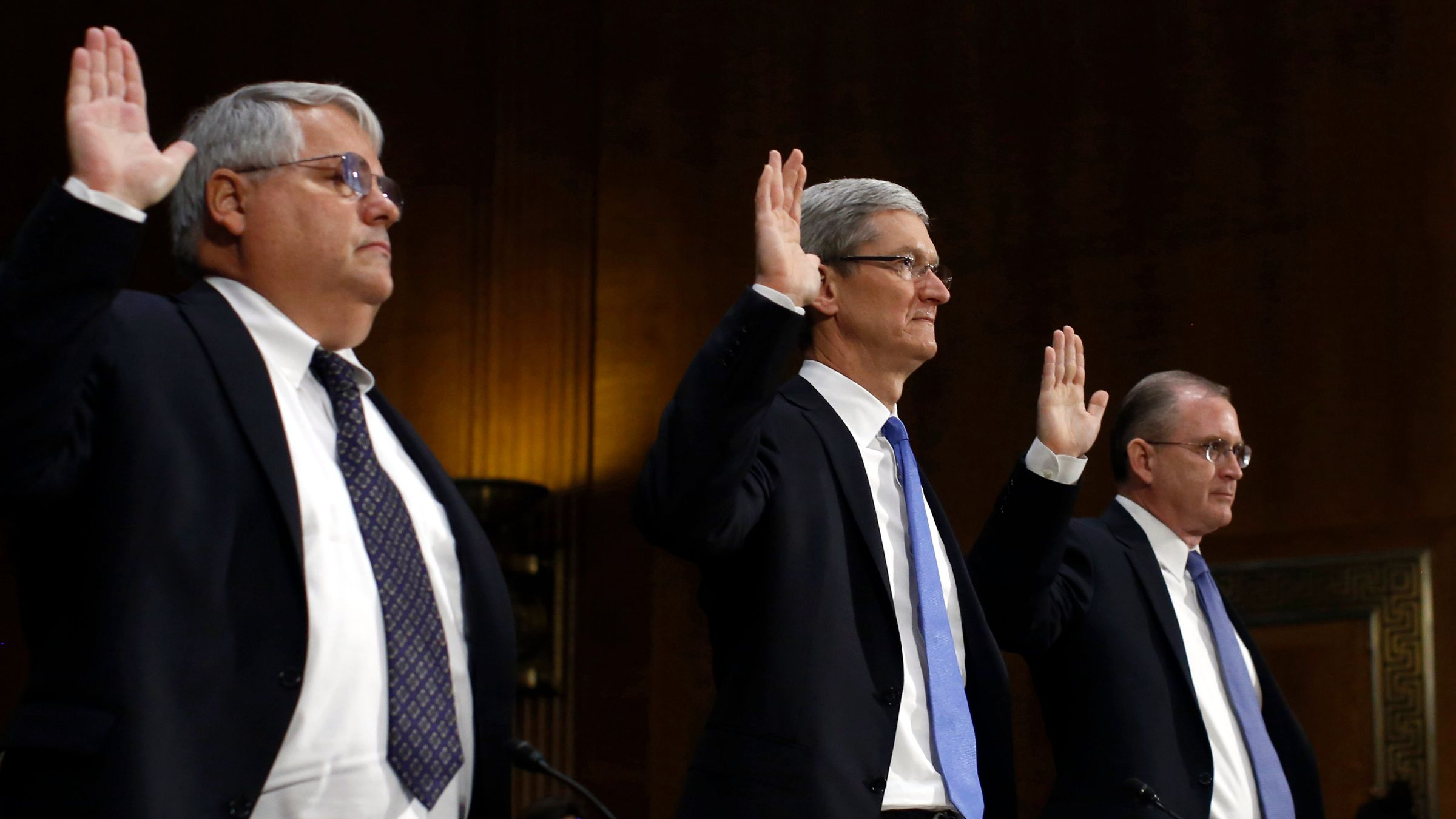 Apple CEO Tim Cook (C) , CFO Peter Oppenheimer (L) and Apple Head of tax operations Philip Bullock are sworn in to testify at a Senate homeland security and governmental affairs investigations subcommittee hearing on offshore profit shifting and the U.S. tax code, on Capitol Hill in Washington, May 21, 2013. Apple Inc came under fire on Tuesday at a Senate hearing over an investigation that alleged the U.S. high technology icon has kept billions of dollars in profits in Irish subsidiaries and paid little or no taxes to any government.