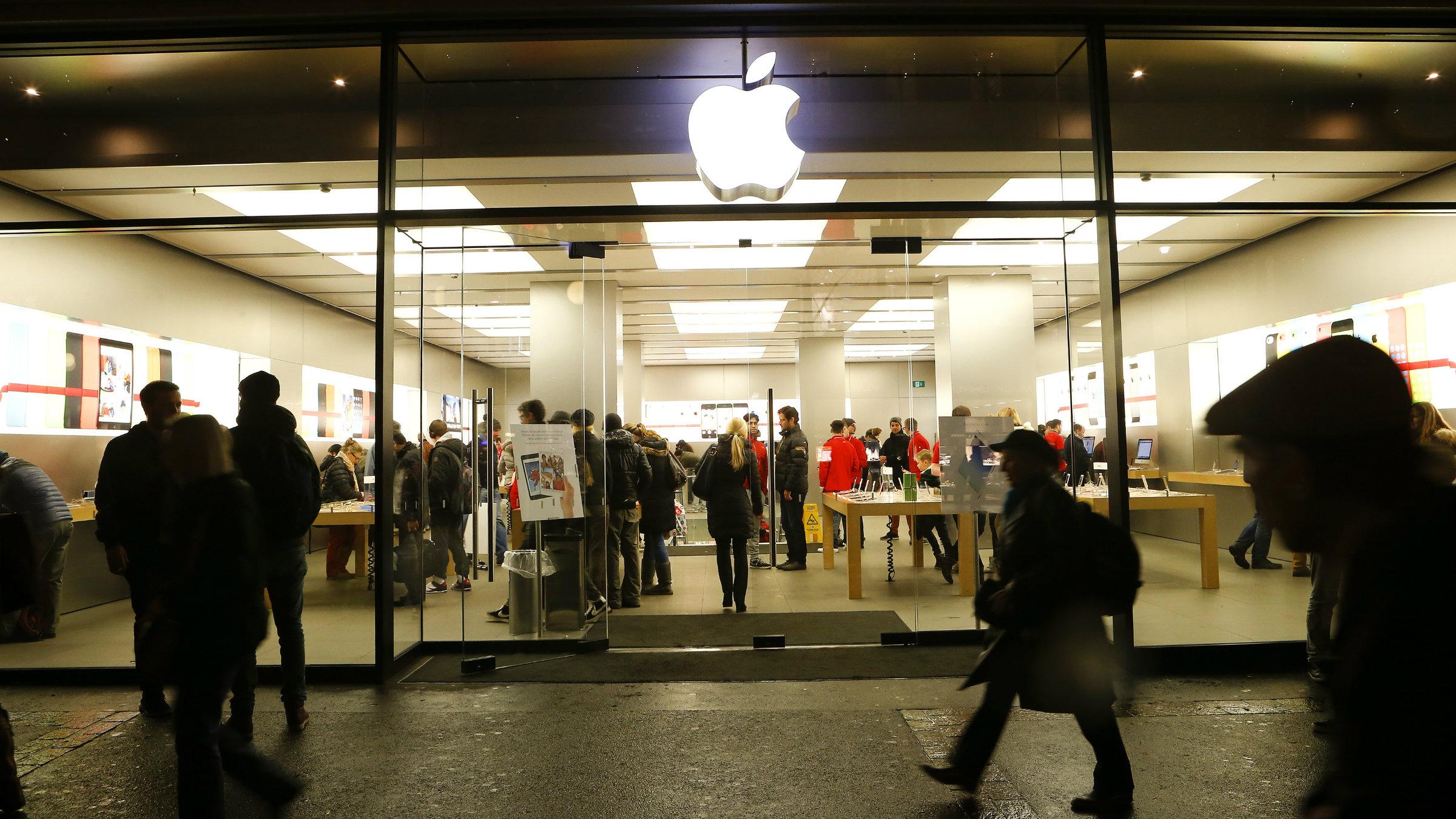 People walk past an Apple Store at the Bahnhofstrasse shopping street in Zurich December 19, 2013. REUTERS/Arnd Wiegmann (SWITZERLAND - Tags: SCIENCE TECHNOLOGY BUSINESS)