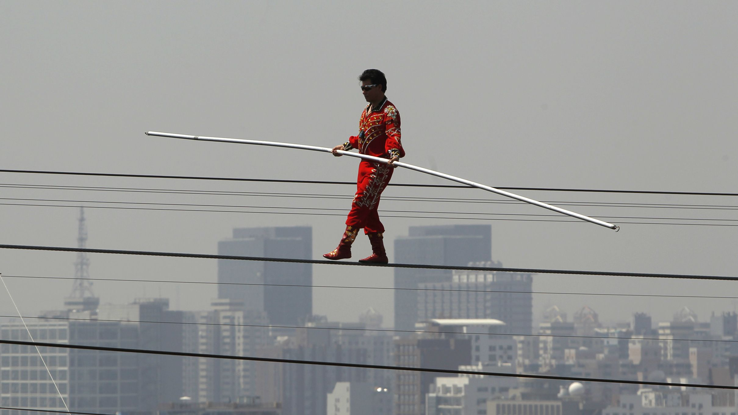 """Adili Wuxor, known as """"Prince of the Tightrope"""", walks the tightrope above the """"Bird's Nest"""" Olympic stadium in Beijing July 2, 2010. Adili on Friday, completed his challenge to break the Guinness World Record for the longest period of time spent living and walking on a tightrope. Adili has been living in a cabin on the roof of the Bird's Nest for the past 60 days, spending 5 hours a day walking the tightrope,local media reported. REUTERS/Bobby Yip"""