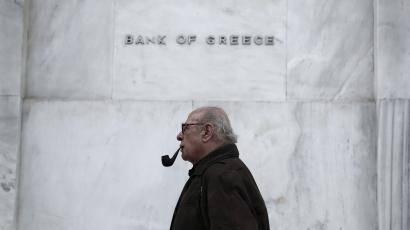 A man walks past the Bank of Greece headquarters, in central Athens on Wednesday, Feb. 4, 2015. With all Europe waiting to see how Greece proposes to renegotiate its massive bailout loans, Greece's Prime Minister Alexis Tsipras and his Finance Minister Yanis Varoufakis are on a whirlwind tour of the region to discuss possible solutions. Tsipras wants easier terms of repayment on the 240 billion euros (currently $271 billion) in bailout loans and to ease back on the austerity budget measures the country has been required to make. (AP Photo/Petros Giannakouris )