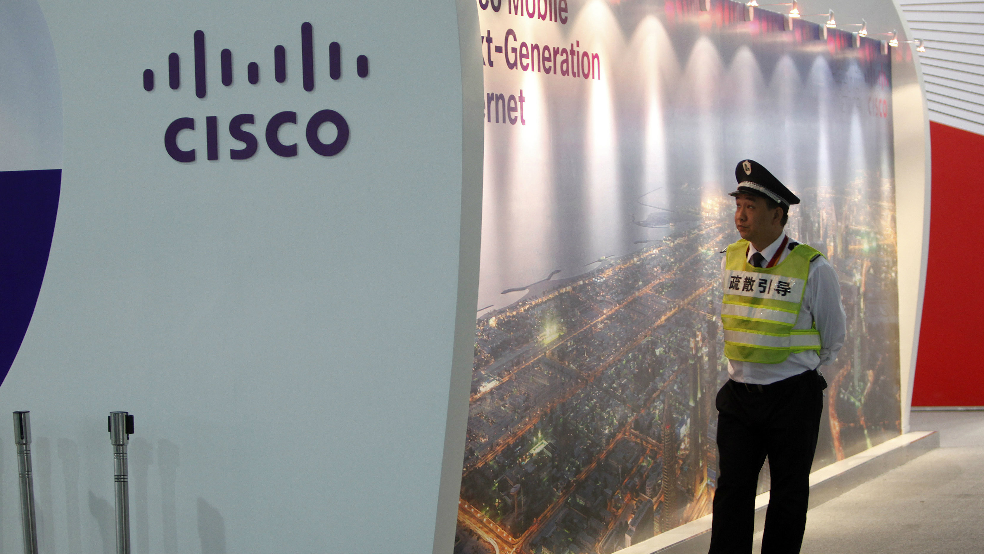 A security guard walks past a Cisco display at the Mobile Asia Expo in Shanghai June 20, 2012. The three-day exhibition opens for the first time in mainland China, to showcase the latest in mobile technology. REUTERS/Aly Song
