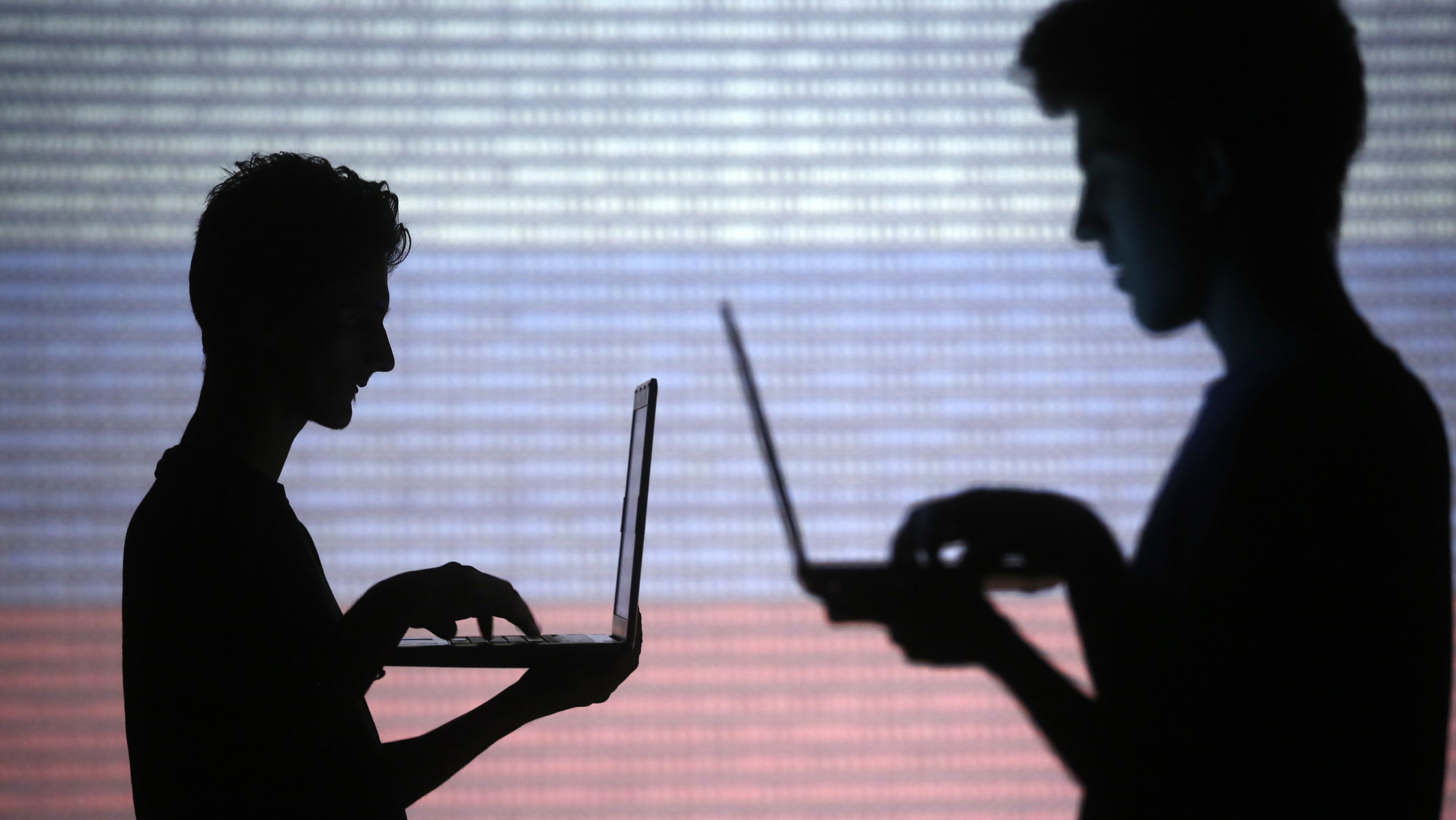 People are silhouetted as they pose with laptops in front of a screen projected with binary code and a Russian national flag, in this picture illustration taken in Zenica October 29, 2014. REUTERS/Dado Ruvic