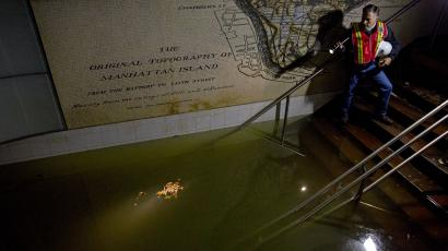 In this Wednesday, Oct. 31, 2012 file photo, Joseph Leader, Metropolitan Transportation Authority vice president and chief maintenance officer, shines a flashlight on standing water inside the South Ferry 1 train station in New York in the wake of Superstorm Sandy. A map of the original topography of Manhattan is seen on the wall behind Leader. By century's end, researchers forecast up to four feet higher seas, producing storm flooding akin to Sandy's as often as several times each decade. Even at current sea levels, Sandy's floodwaters filled subways, other tunnels and streets in parts of Manhattan. (AP Photo/Craig Ruttle