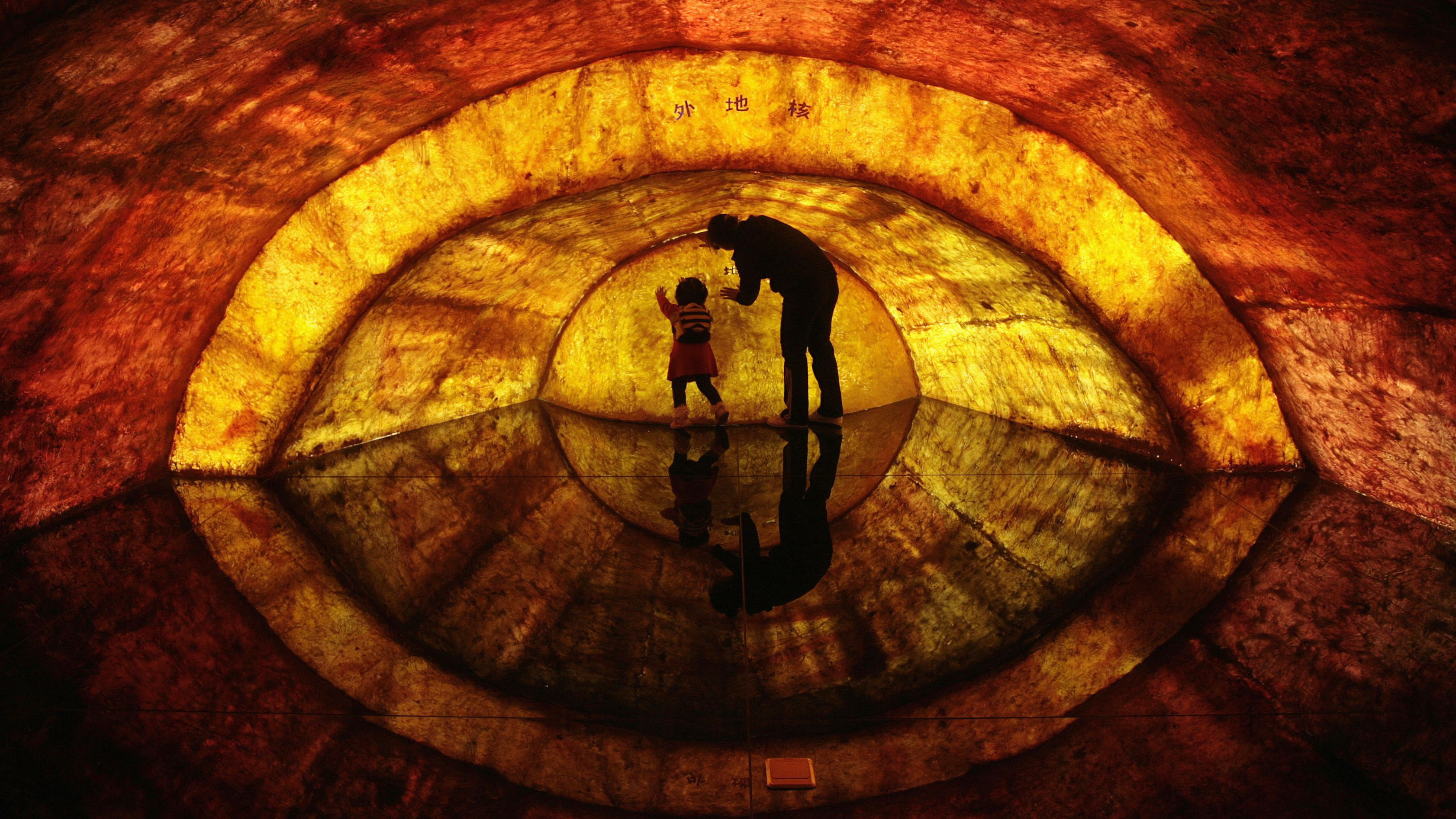 """A woman and her daughter touch a structural model of the earth's core at Nanjing Geological Museum in Nanjing, Jiangsu province April 22, 2011. Earth Day, which is celebrated on April 22 every year, marks an annual effort to raise public awareness about the environment and inspire actions to clean it up. The Chinese characters on the model read """"outer core"""". REUTERS/Sean Yong (CHINA - Tags: SOCIETY ANNIVERSARY ENVIRONMENT IMAGES OF THE DAY) - RTR2LHTC"""