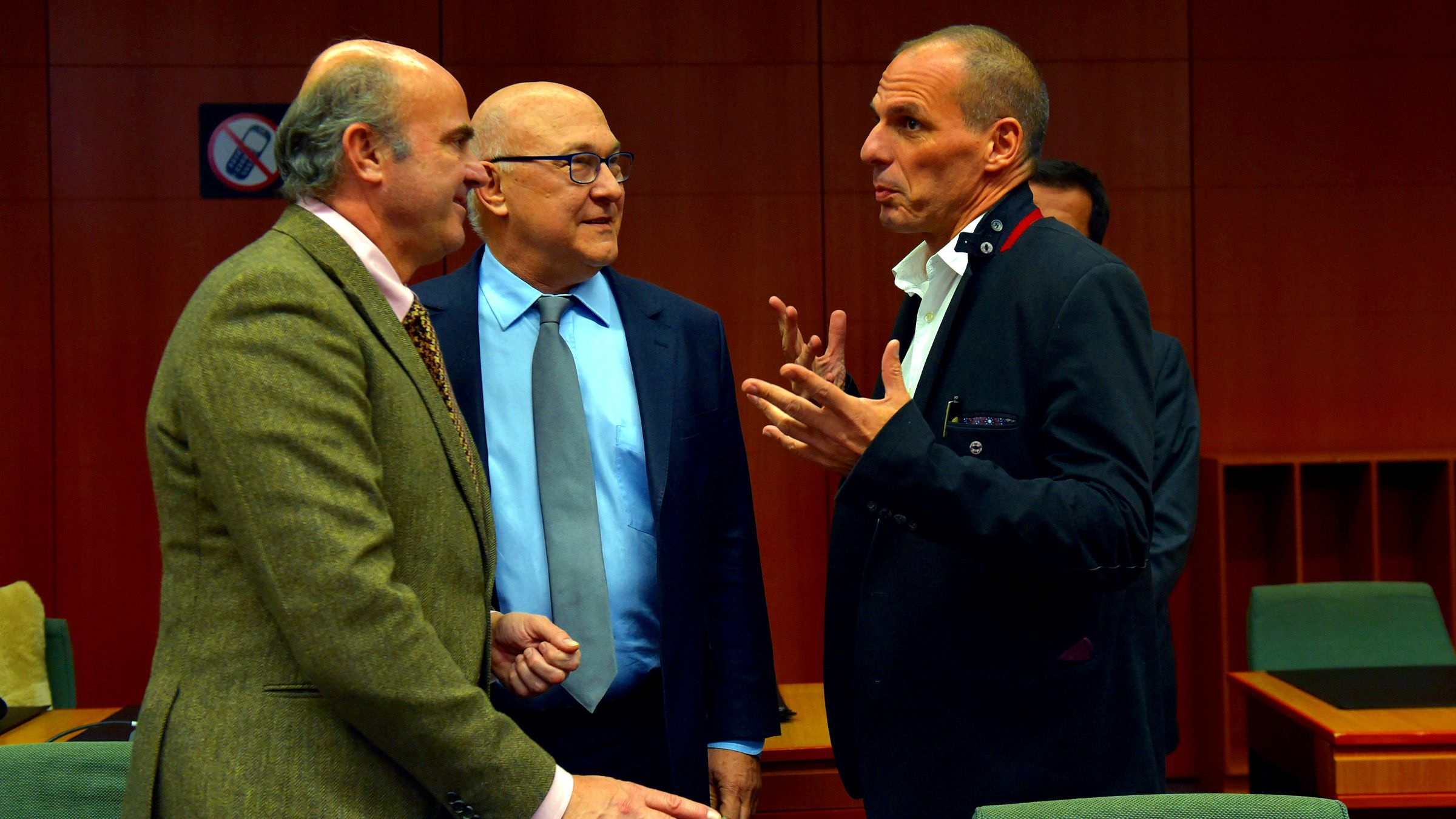 (L-R) Spain's Finance Minister Luis de Guindos and France's Finance Minister Michel Sapin chat with Greece's Finance Minister Yanis Varoufakis during an extraordinary euro zone finance ministers meeting (Eurogroup) to discuss Athens' plans to reverse austerity measures agreed as part of its bailout, in Brussels February 20, 2015. Euro zone finance ministers reached an agreement on Friday to extend heavily indebted Greece's financial rescue by four months, officials on both sides said.