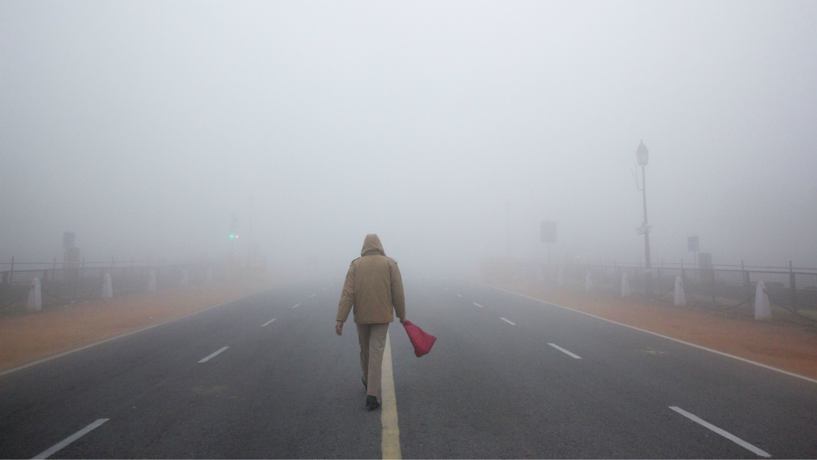 A Delhi police officer with red flag walks ahead of his marching contingent during the upcoming Republic Day parade practice amidst morning fog in New Delhi, India, Monday, Dec. 29, 2014. U.S. President Barack Obama will travel to India to participate in Indian Republic Day celebration as chief guest, which will be celebrated on Jan. 26, 2015. (AP Photo /Manish Swarup)