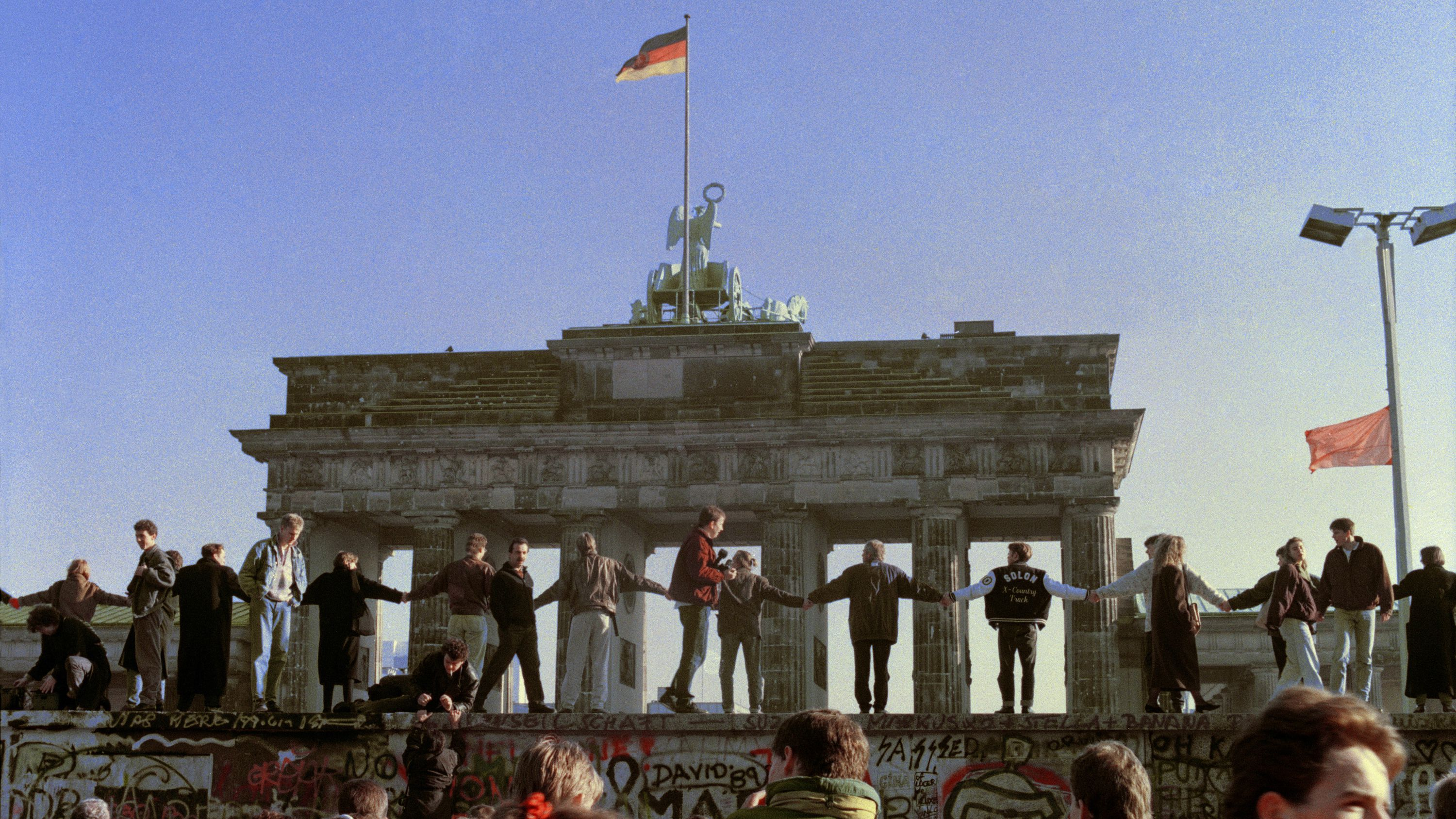 Berliners sing and dance on top of The Berlin Wall to celebrate the opening of East-West German borders in this Nov. 10, 1989 file picture. Thousands of East German citizens moved into the West after East German authorities opened all border crossing points to the West. In the background is the Brandenburg Gate. Built in 1961 of barbed wire and concrete, the wall divided Berlin, becoming the most powerful symbol of The Cold War. Thursday, Nov. 9, 2006 marks the 17th anniversary of the fall of the Berlin Wall. (AP Photo/Thomas Kienzle, File)