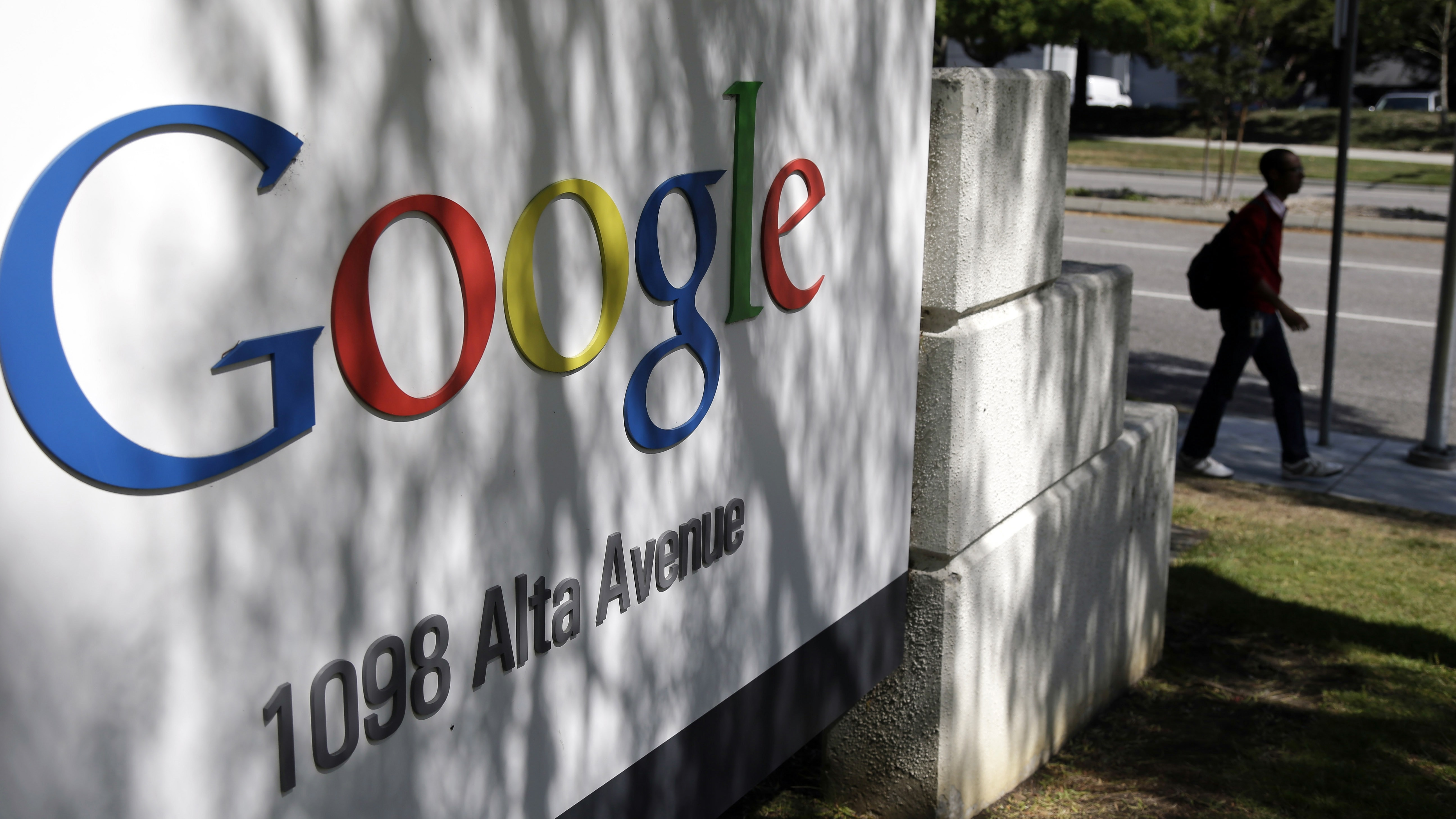 In this June 5, 2014 file photo, a man walks past a Google sign at the company's headquarters in Mountain View, Calif., U.S.A. The politically-fraught issue of forcing big, multinational companies to pay more tax will be high on the agenda at G-20 summit on Nov. 15 and 16 in Brisbane, Australia. There has been an ongoing effort by governments to crack down on tax avoidance, with companies such as Google and Amazon facing criticism for moving profits earned in one country to other countries with lower tax rates. (AP Photo/Marcio Jose Sanchez, File)