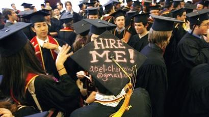 graduates with hire me sign