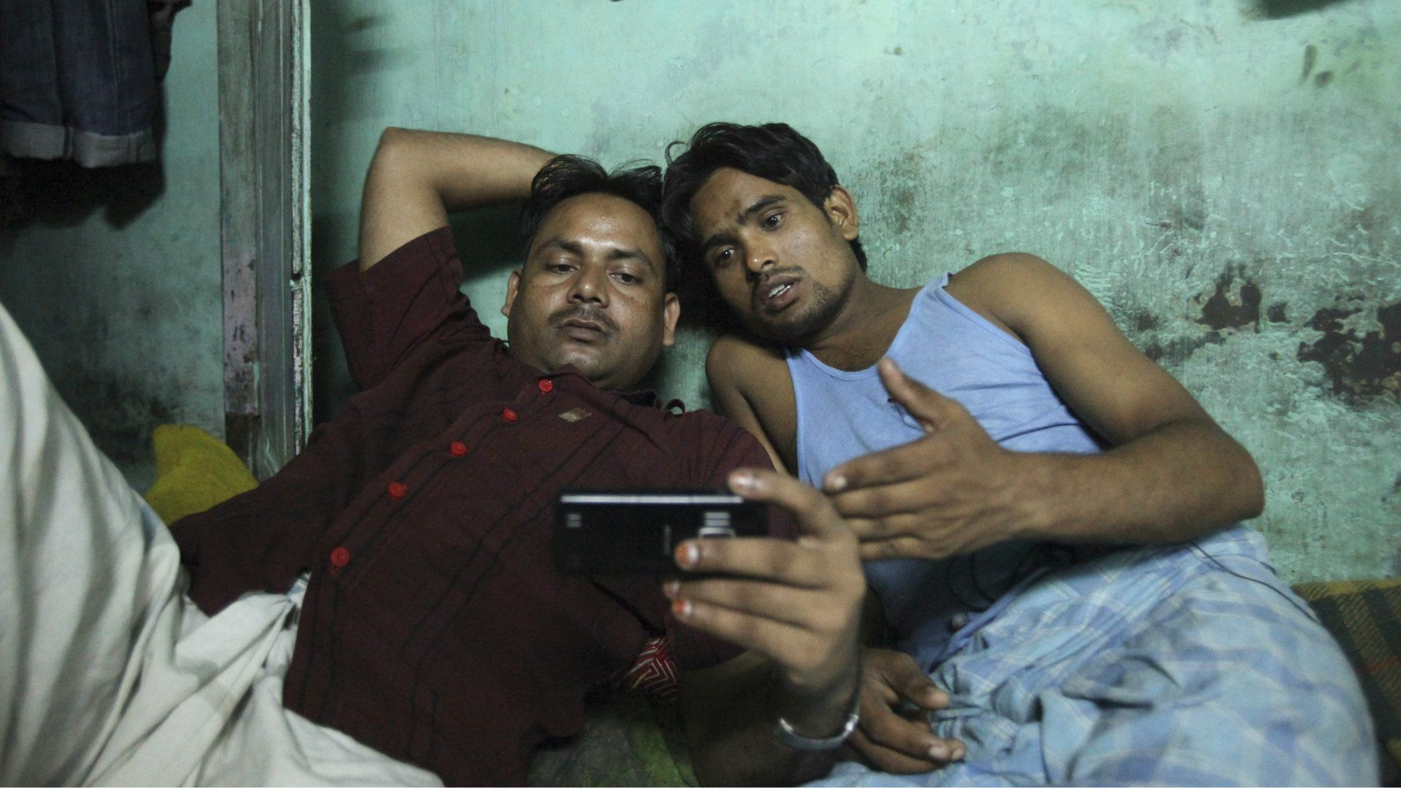 Migrant workers watch movie on a mobile phone in their one room dwelling in a residential area in Mumbai October 3, 2011. Ten migrant workers who pay a monthly rent of 6,000 rupees ($123) live in a 4.5 x 3 metres (15 x 10 ft.) room. All the occupants who come from the same district of the northern Indian state of Uttar Pradesh are in Mumbai for better job opportunities and work as taxi drivers and manual labourers. According to a 2011 census conducted by the government of India, the population of Mumbai is more than 12 million and there is estimated to be about 20,482 persons per square kilometre. Picture taken October 3, 2011. REUTERS/Danish Siddiqui (INDIA - Tags: SOCIETY BUSINESS EMPLOYMENT)